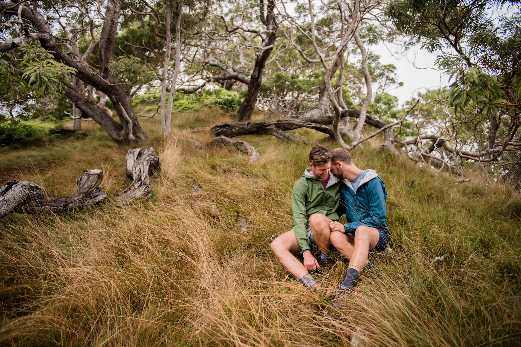 LGBTQ couple holding each other sitting down on a hiking trail in Kauai, Hawaii