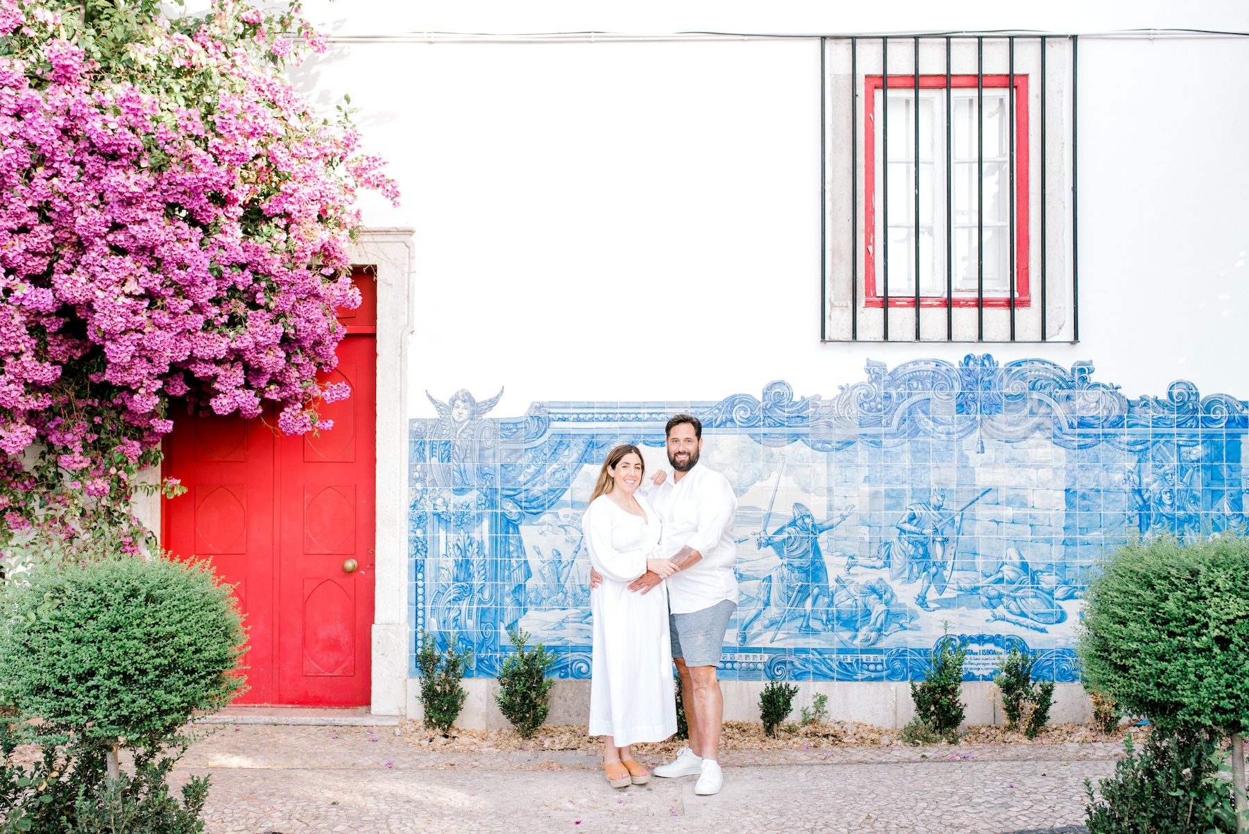 pregnant couple standing in front of a colourful building in Lisbon, Portugal