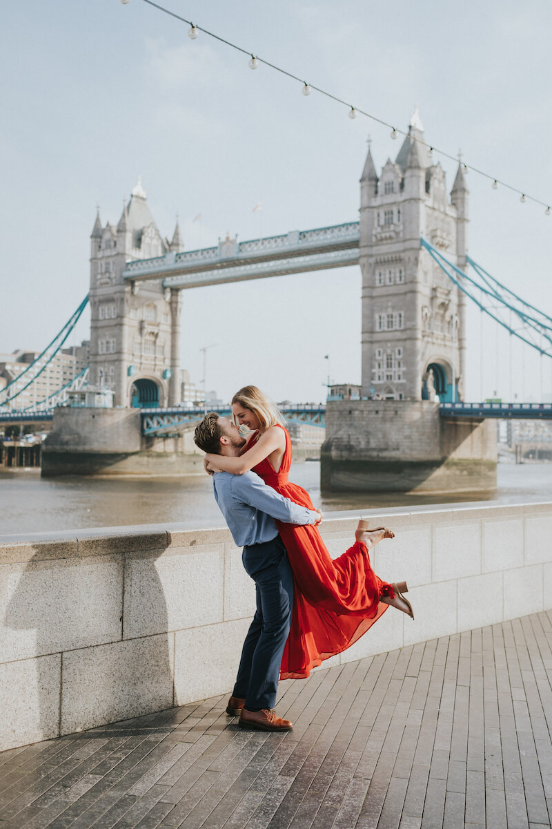 a man is lifting a woman in front of the tower bridge in London, England
