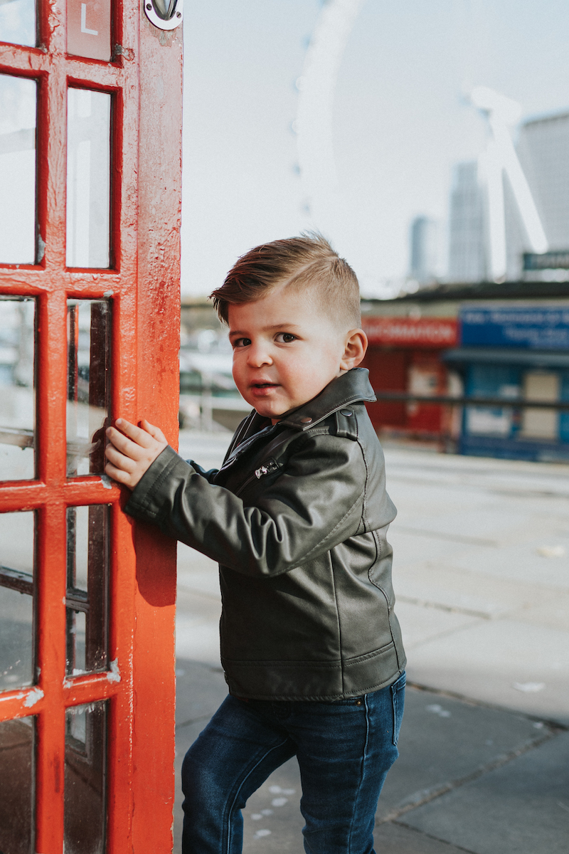 a small boy entering a phone booth in London, England