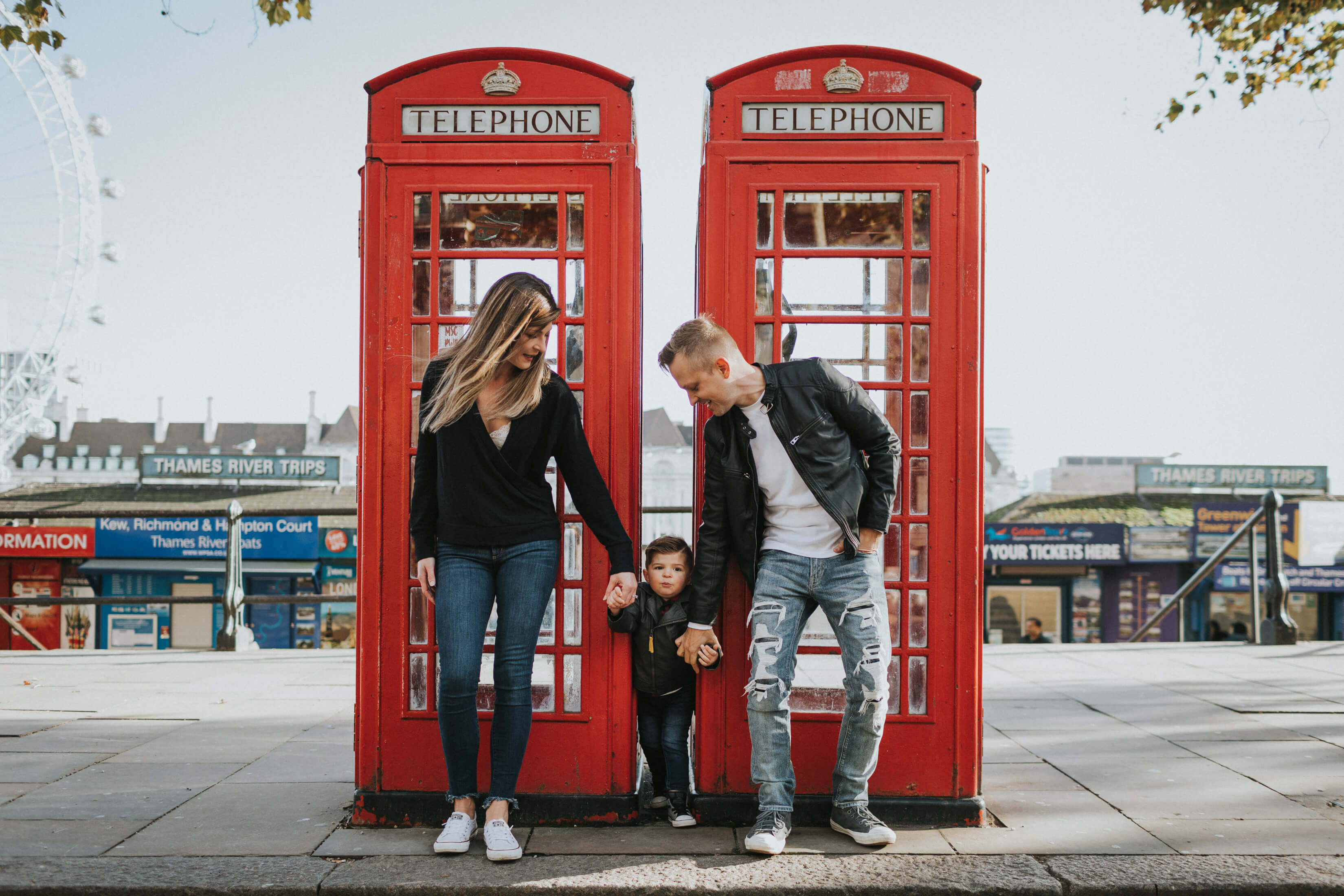 family of three, with a small boy standing in front of a red phone booth in London, England