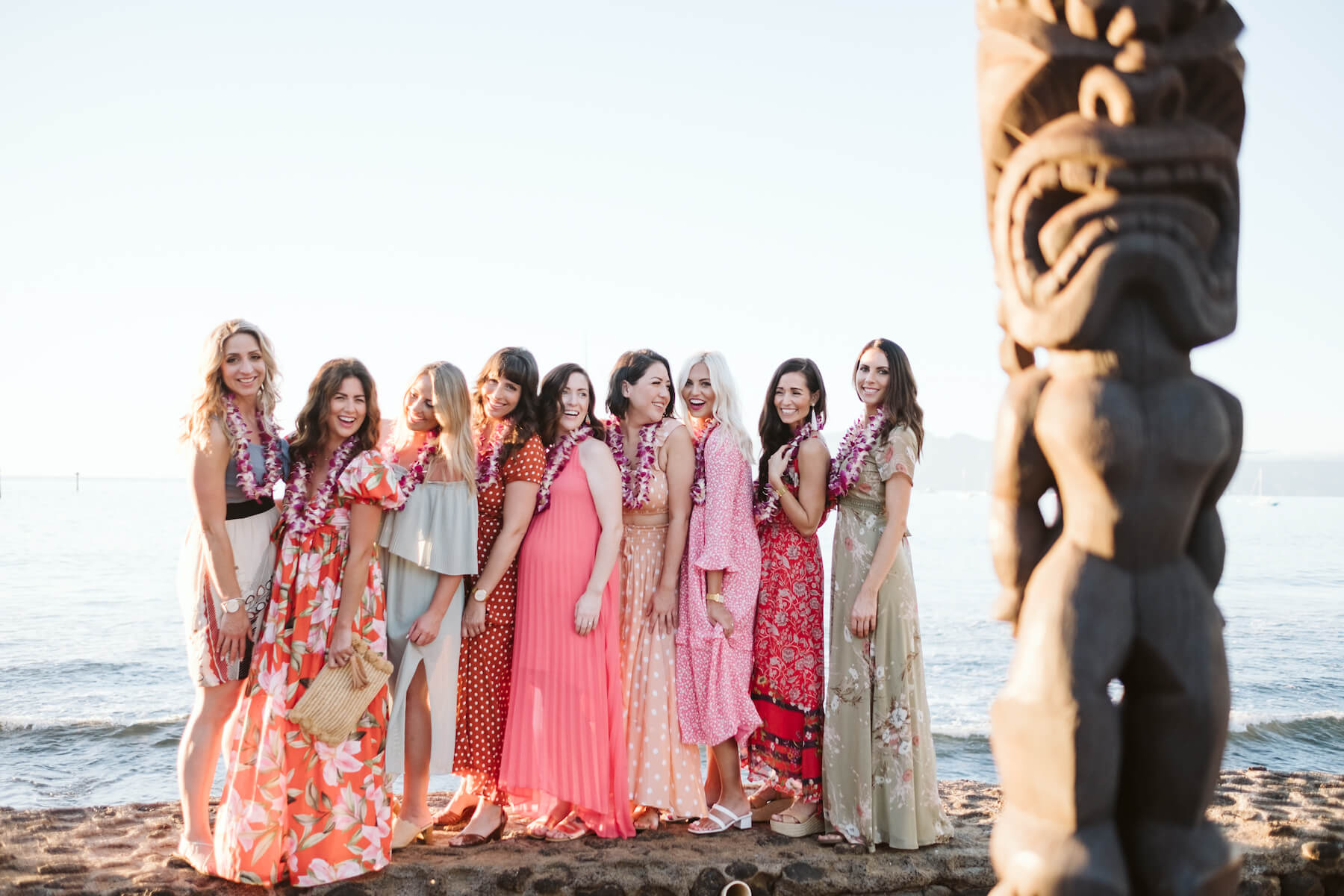 9 girlfriends on a girls trip are standing on the beach wearing colorful dresses and having fun in Maui, Hawaii