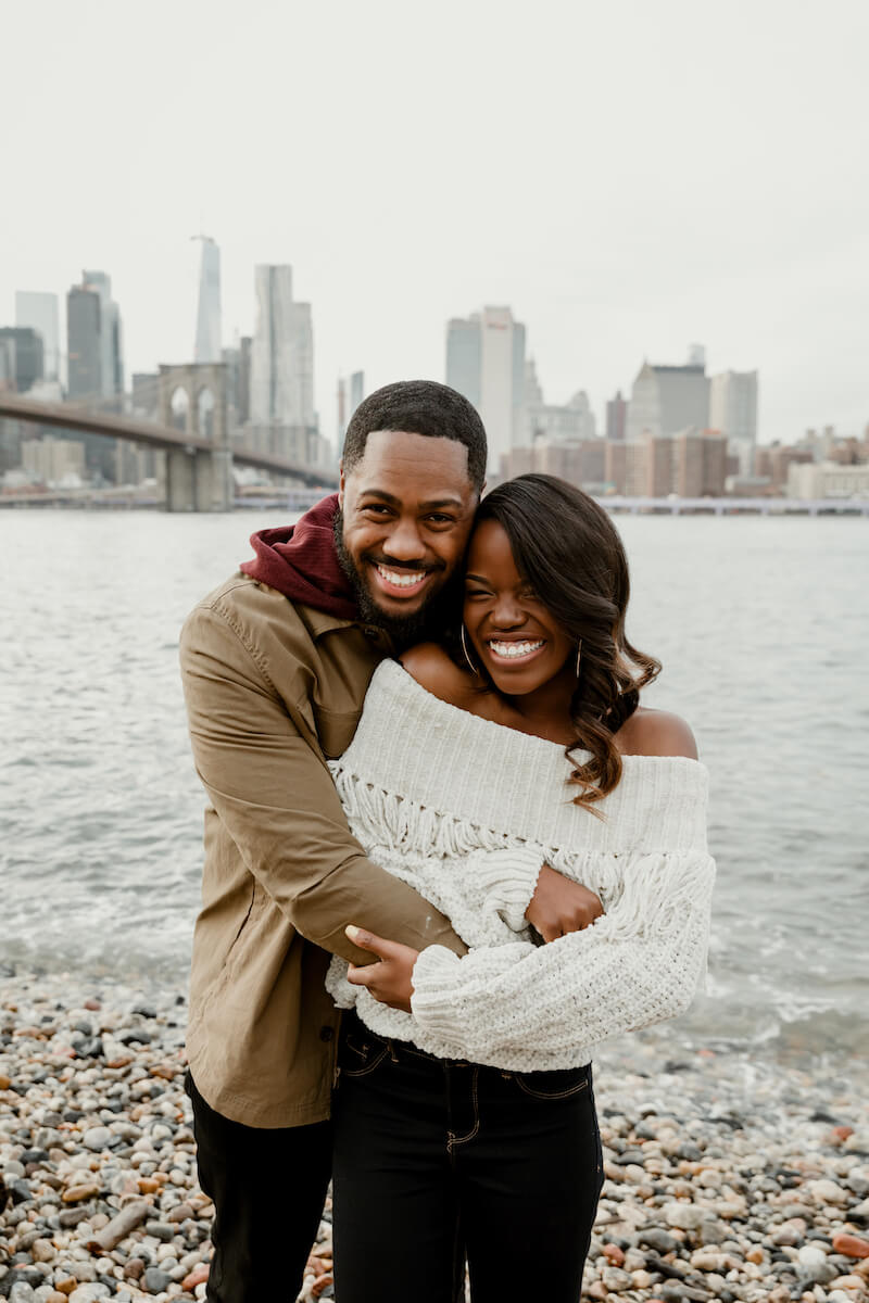 couple hugging and standing with NYC bridge in the background in New York City, New York