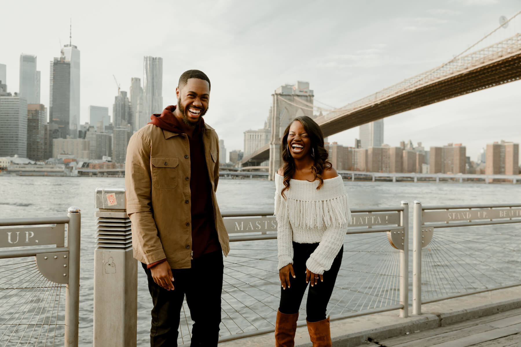 couple on a pier in NYC with the bridge and city in the background in New York City, New York