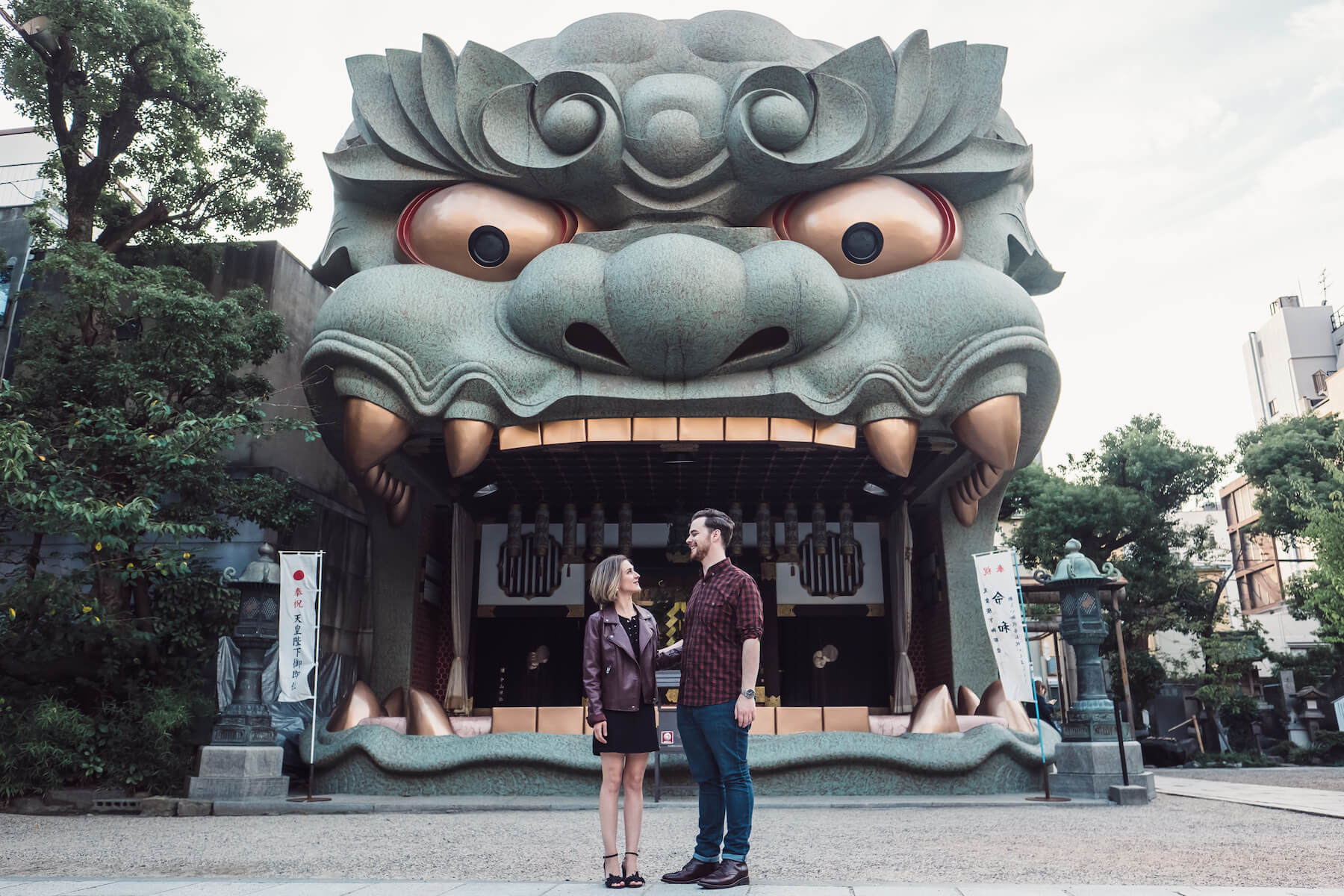 couple looking at each other in front of a statue of a dragon in Osaka, Japan