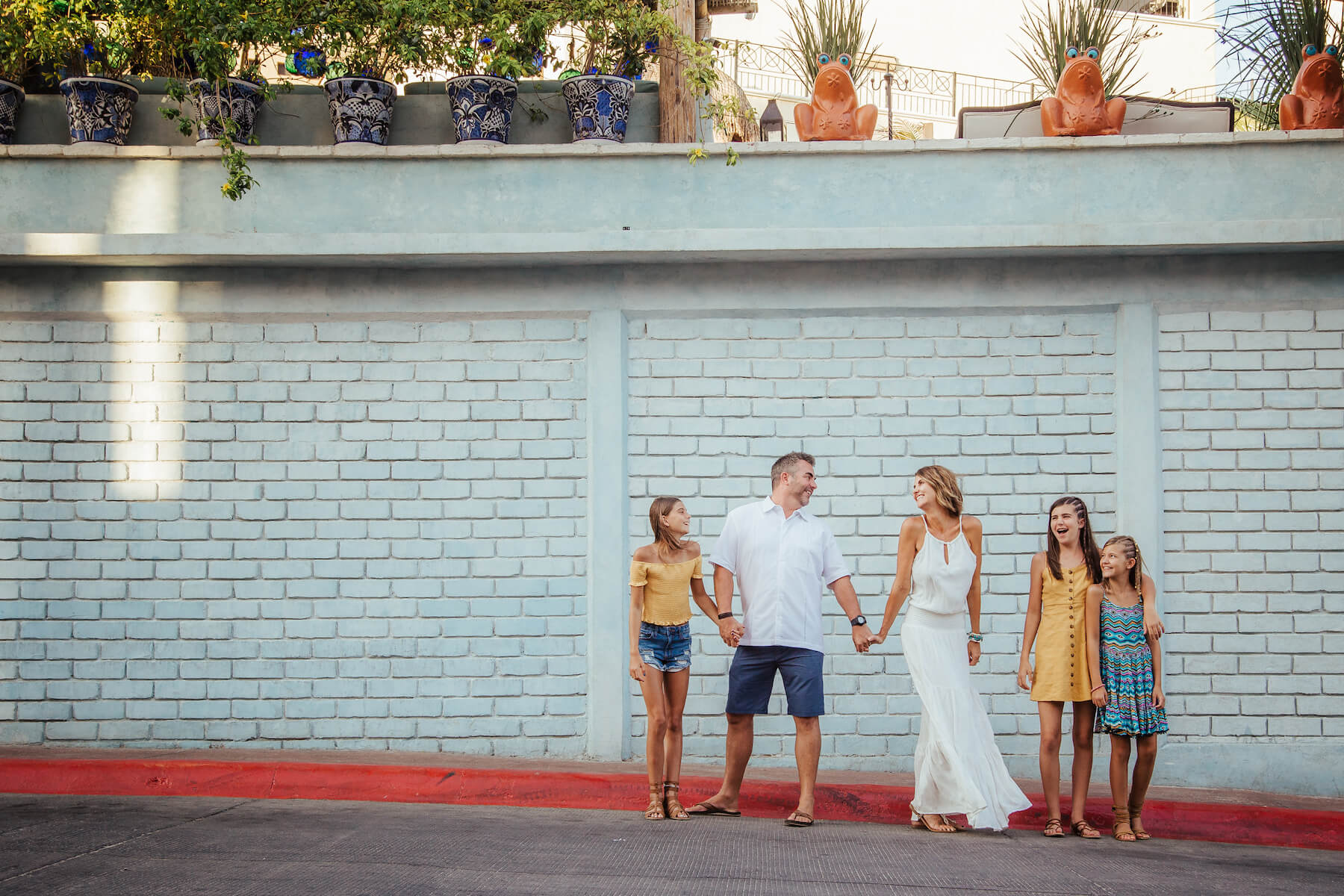 family of five standing in front of a colourful building in Cabo San lucas, Mexico