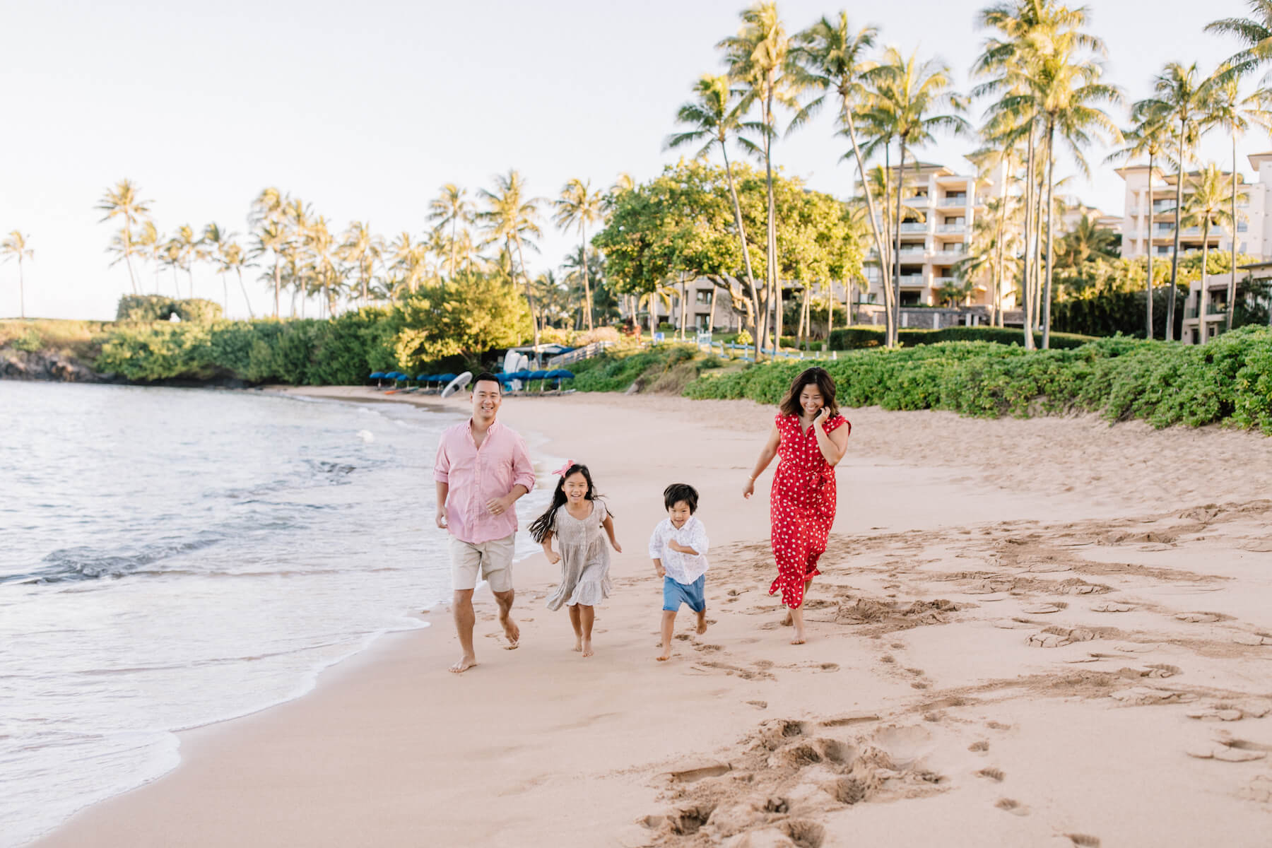 family of four running on the beach in Maui, Hawaii