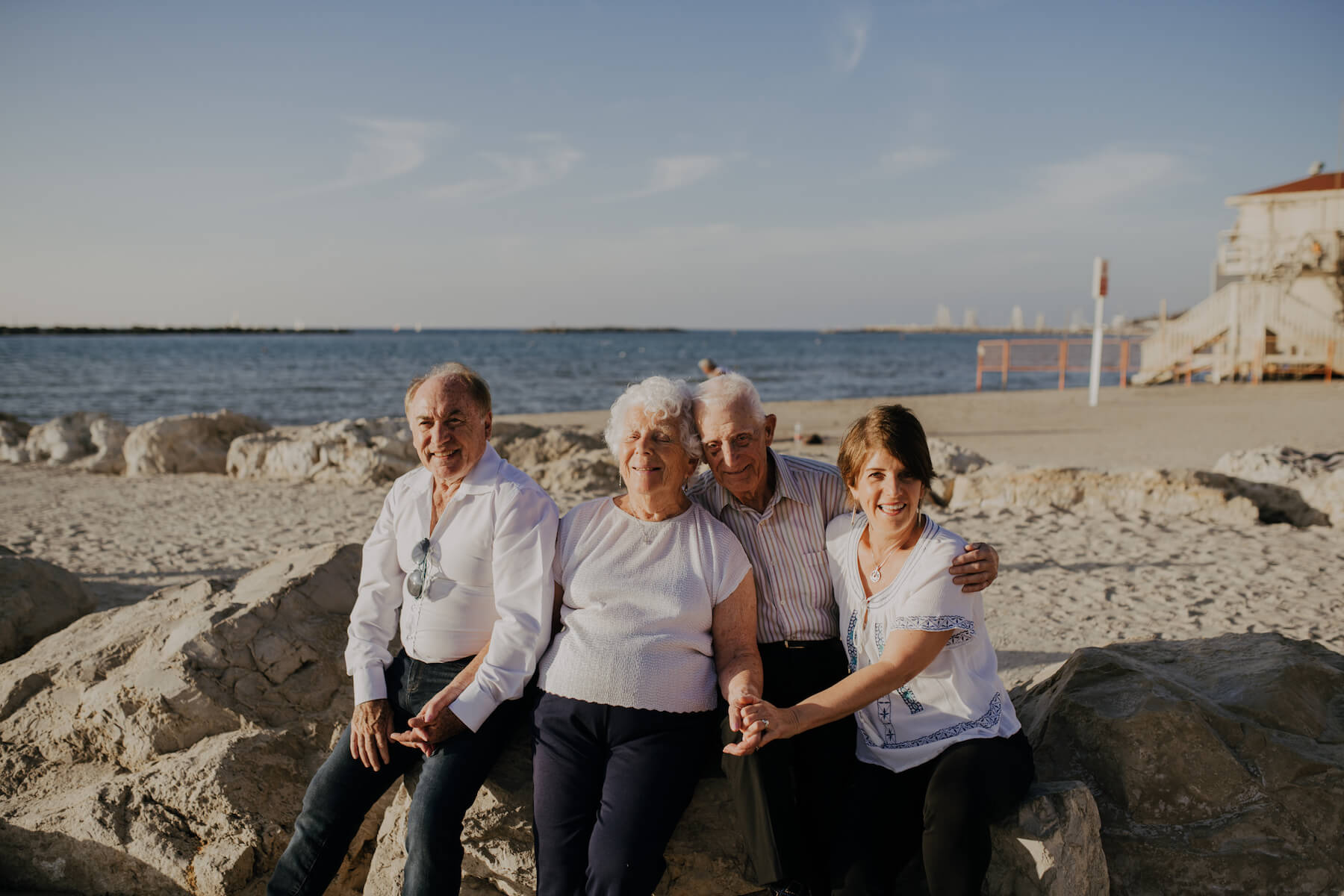 family of 4 sitting on a rock on the beach in Tel Aviv, Israel