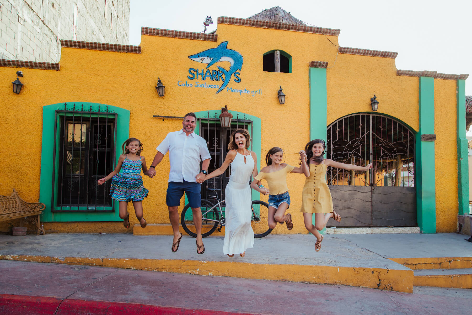 family of five holding hands and jumping in front of a colourful building in Cabo San Lucas, Mexico