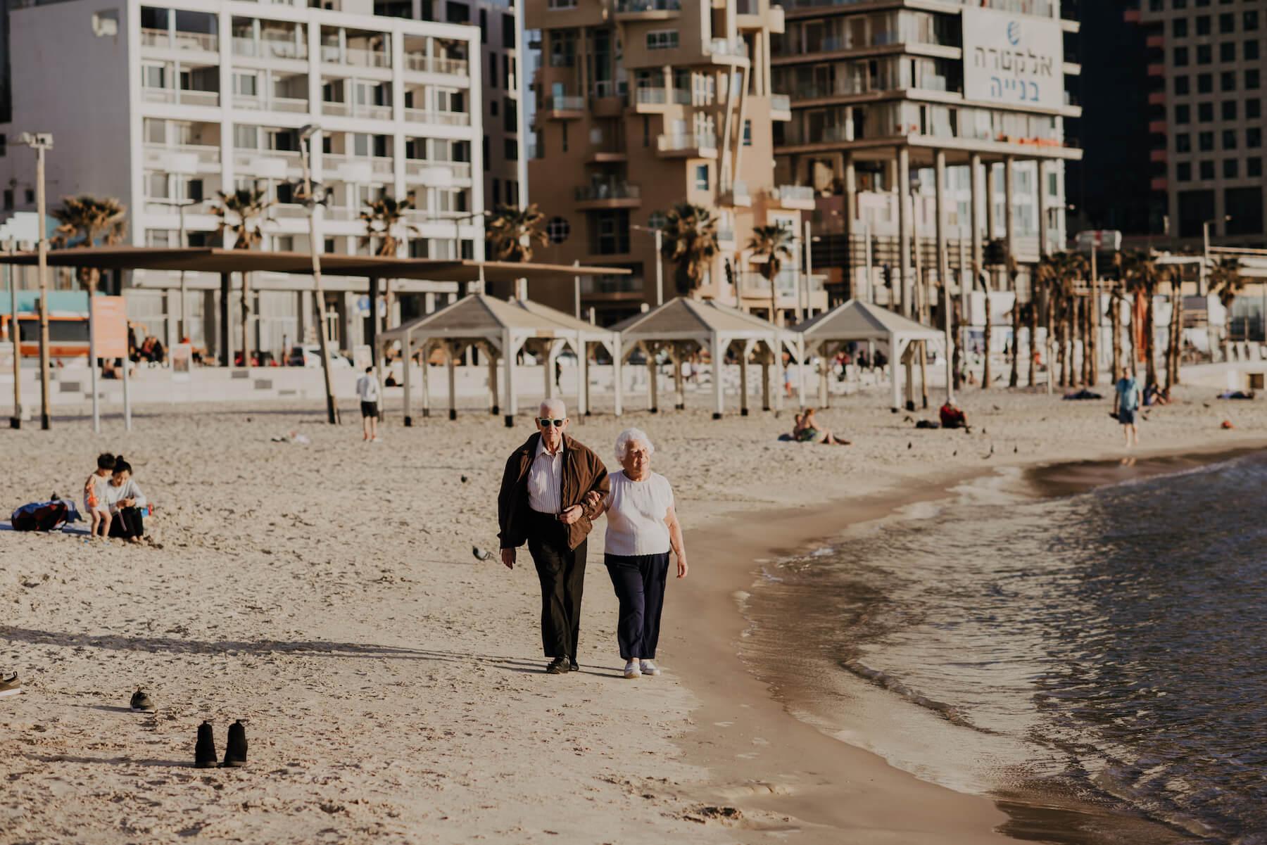 Older couple walking on the beach in Tel Aviv, Israel