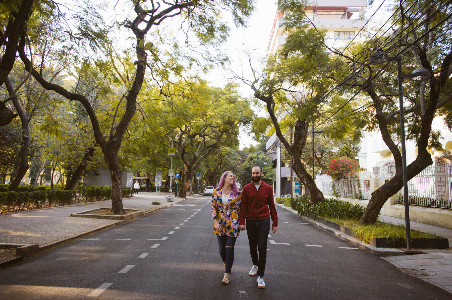 couple holding hands and walking down the middle of a road in Mexico City, Mexico