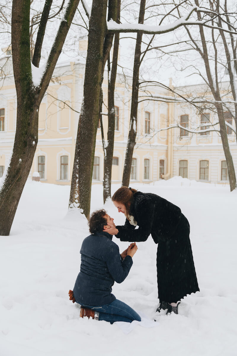 the man is proposing to the woman, he is kneeling in the snow and she is bending over with excitement in St. Petersburg, Russia