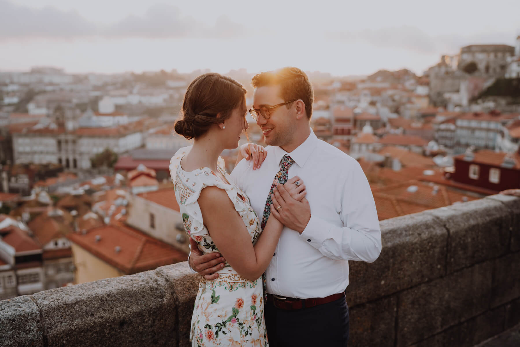 couple holding hands and hugging, with the city of Porto in the background in Porto, Portugal