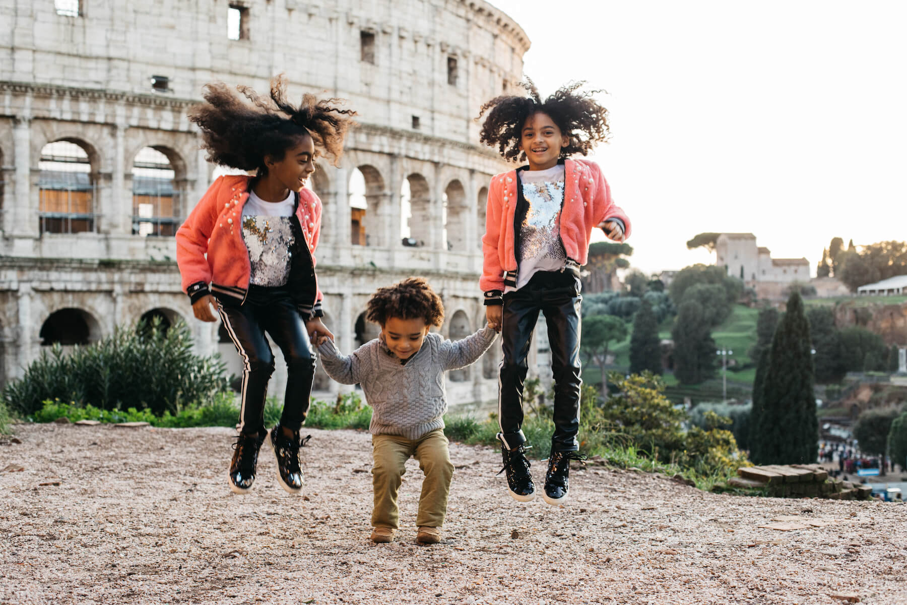 a brother and two sisters jumping in front of the colosseum in Rome, Italy