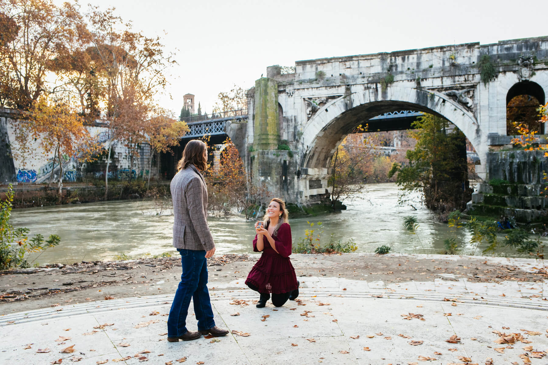 a woman is proposing to a man, she is on one knee in Rome, Italy