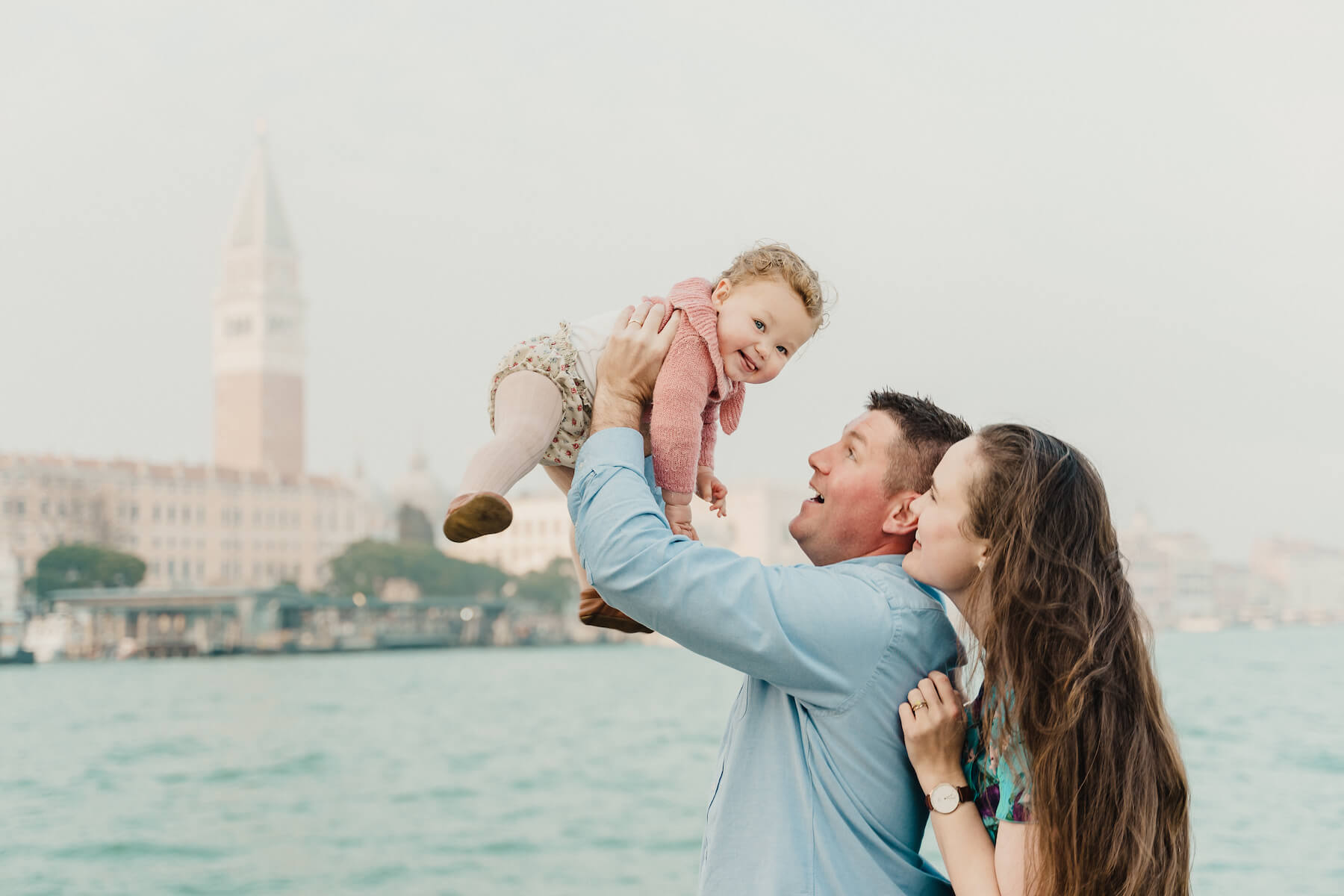 a family of three, the man is holding the baby up in the air with Venice canal in the background in Venice, Italy