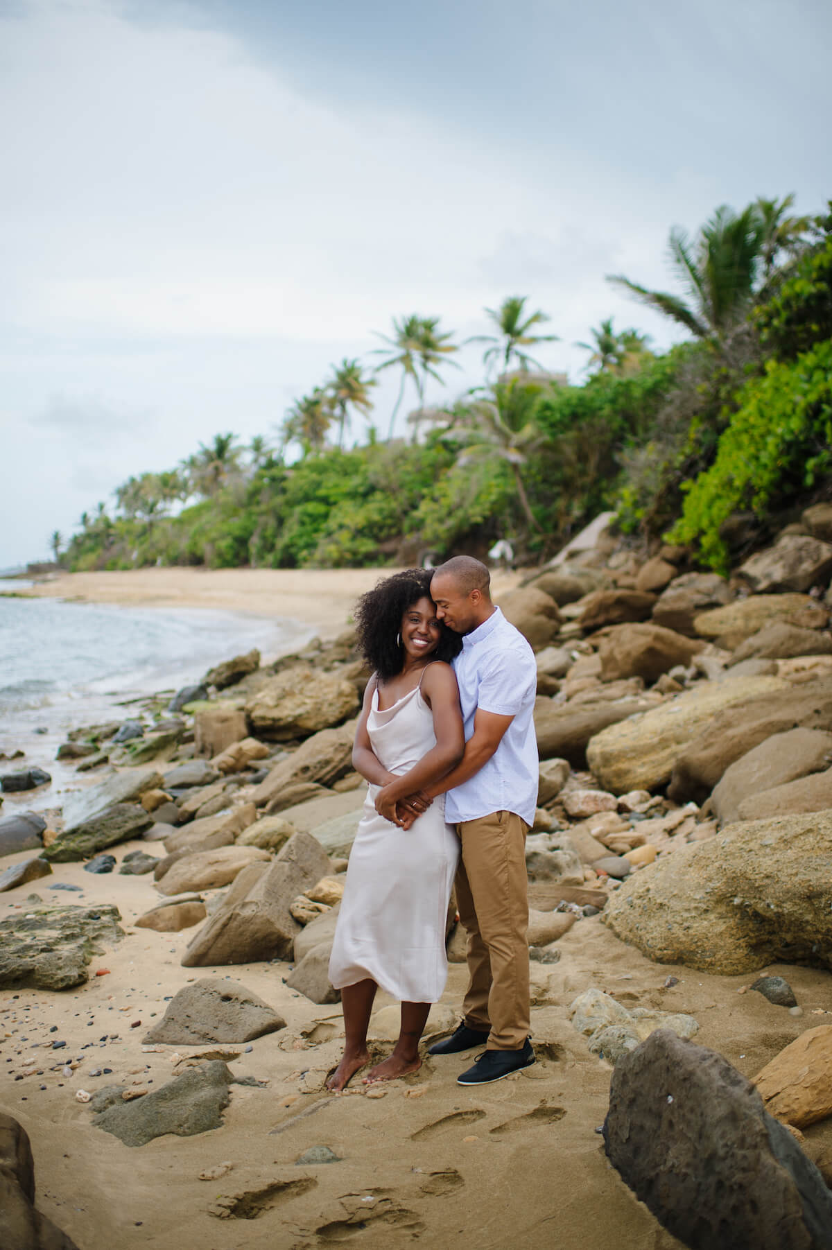 A man and a woman hold each other closely and smile while standing on a beach in San Juan, Puerto Rico.