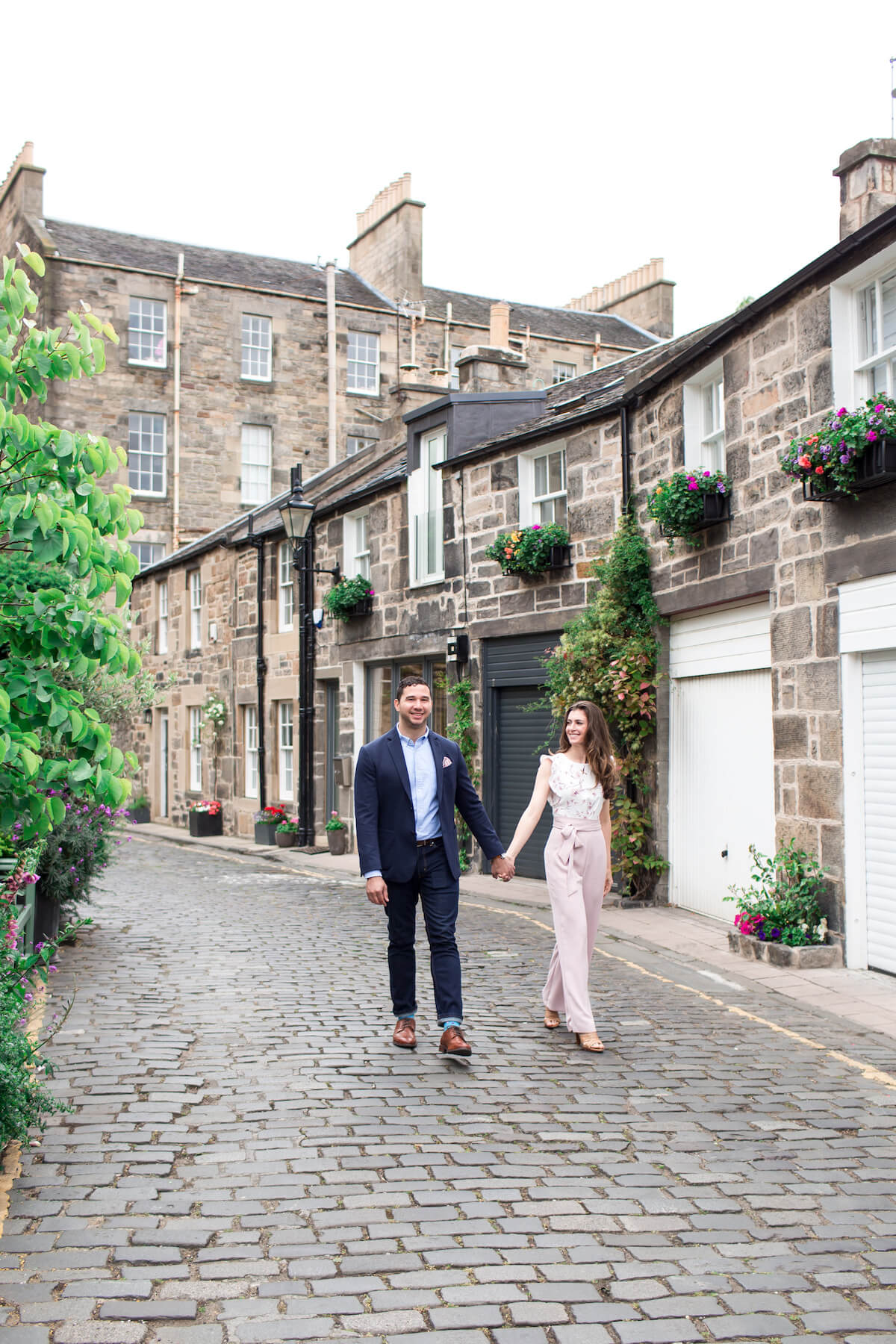 A well-dressed couple hold hands while walking along a picturesque street in Edinburgh, Scotland.