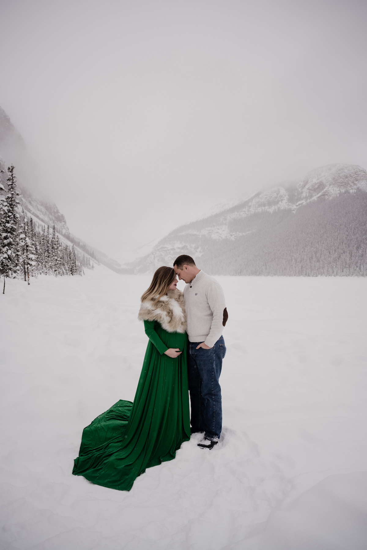 A pregnant woman in a long green dress and a man in a white sweater standing together holding each other in a snowy landscape in Lake Louise, Canada.