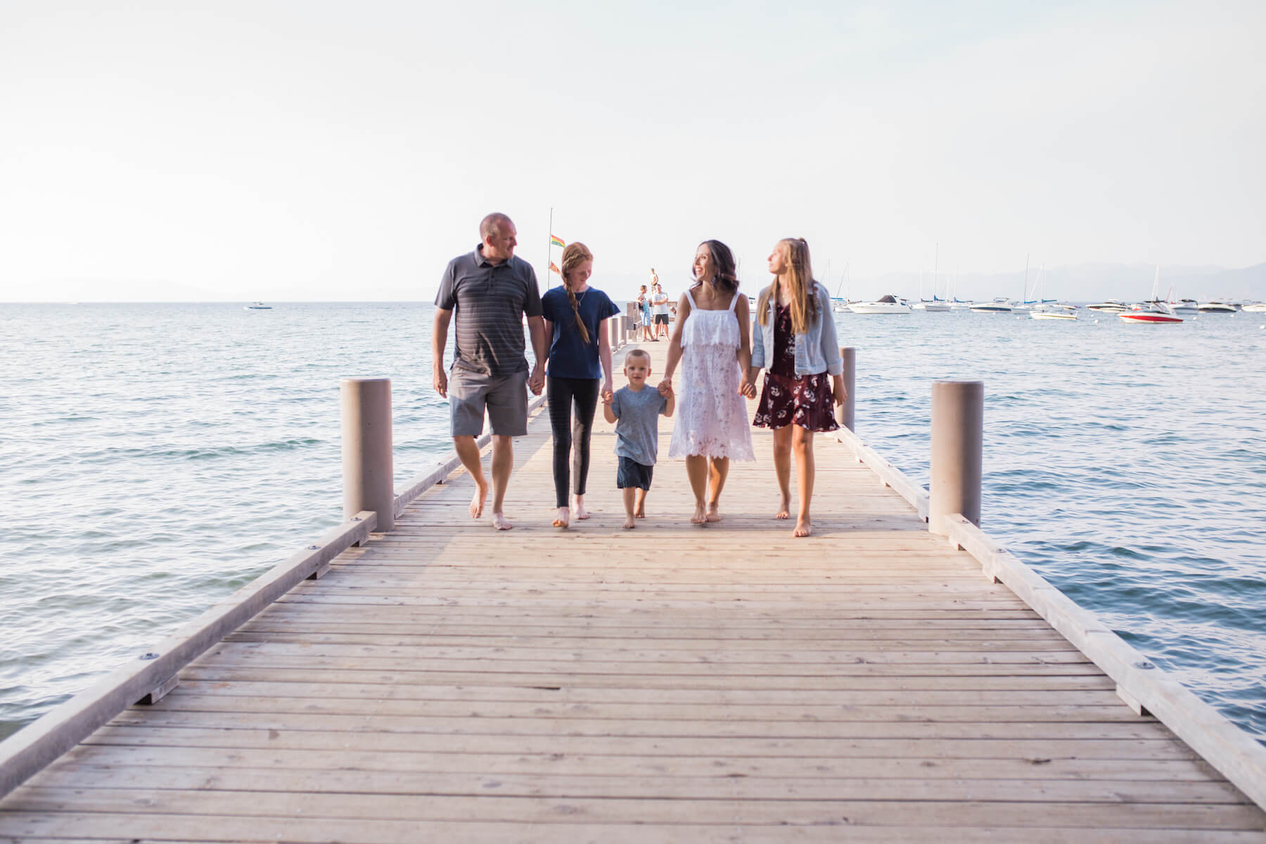 Family of 5 walking on a dock in Lake Tahoe United States USA