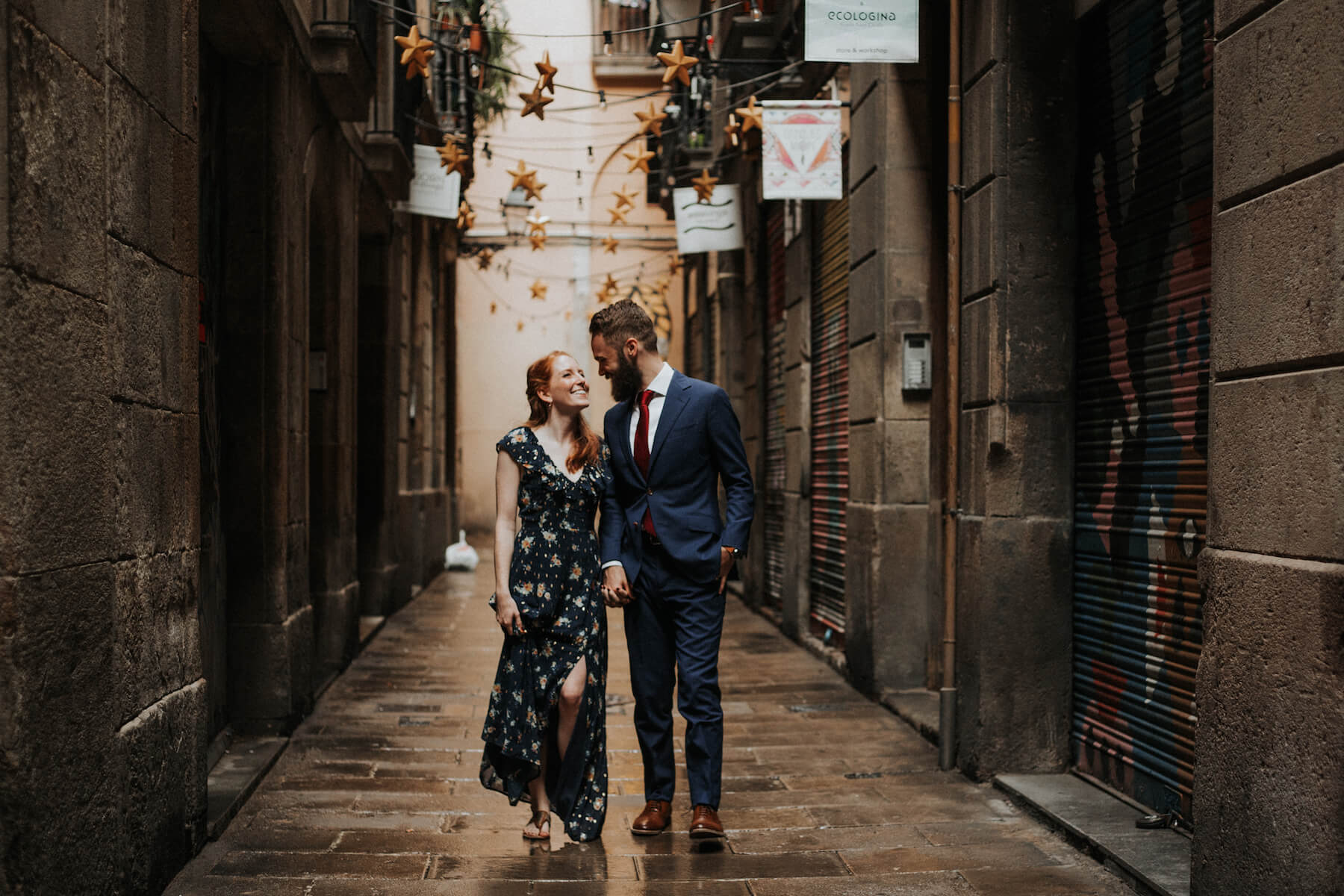 A well-dressed man and woman holding hands and smiling at each other while walking through the streets of Barcelona, Spain.