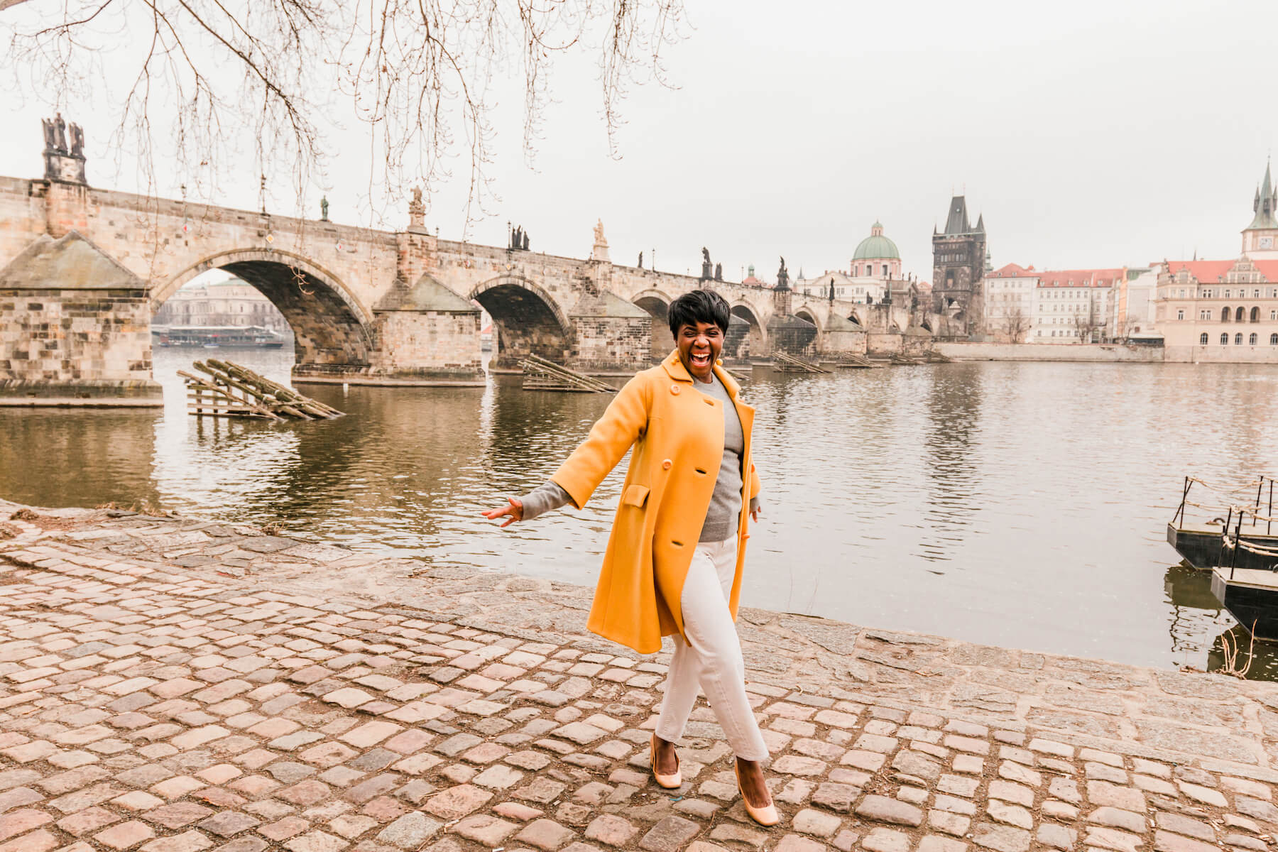 A woman smiling and dancing in a bright yellow jacket on the bank by the river in Prague, Czech Republic.