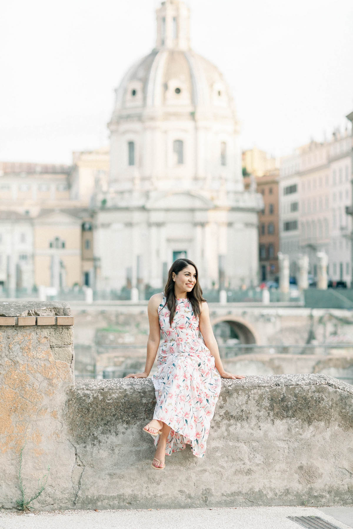 A young woman in a pretty floral dress sitting on a wall in front of iconic buildings in Rome, Italy.