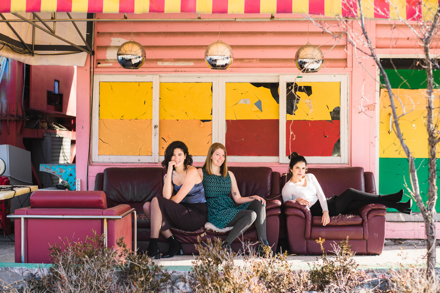 Three well-dressed young women posing on colourful furniture in an abandoned amusement park in Seoul ,South Korea.