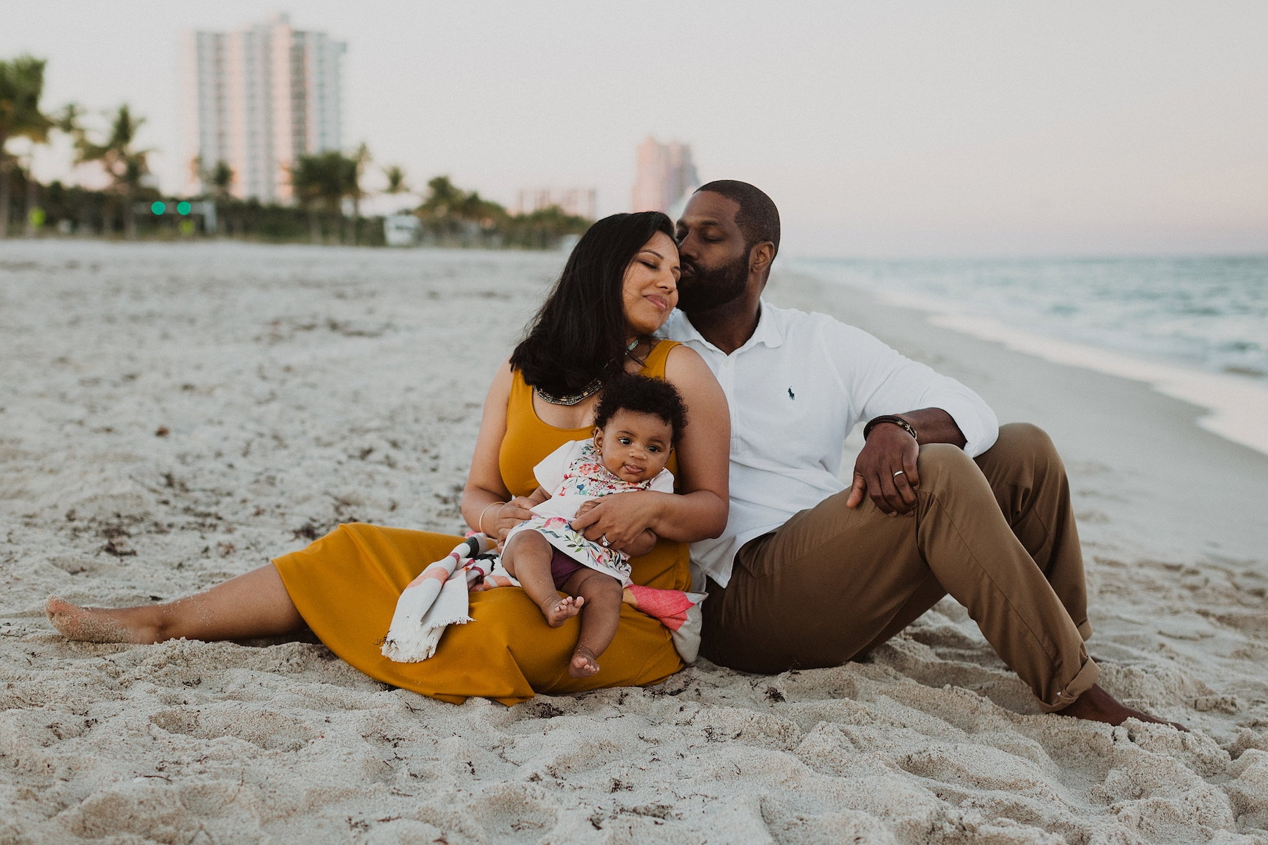 A man kisses the side of his wife's forehead while they sit on the beach with their baby in Ft Lauderdale, USA.