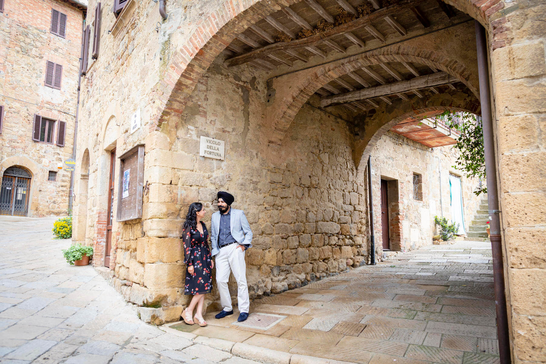 A man and woman look at each other and smile while leaning against a stone wall in Tuscany, Italy.