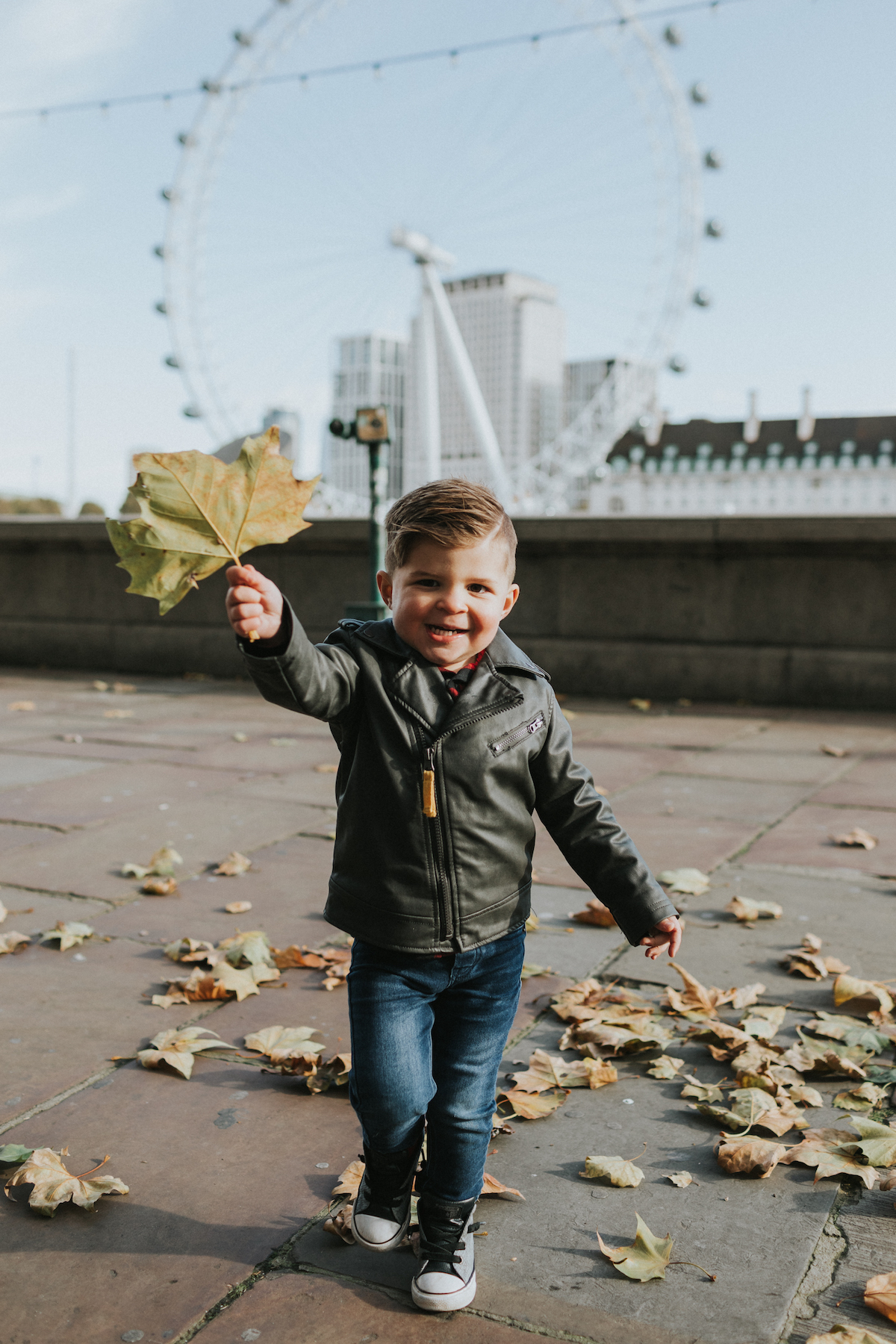 A 2-year-old boy wearing a leather jacket and jeans, smiling and holding a colourful leaf in London, UK.