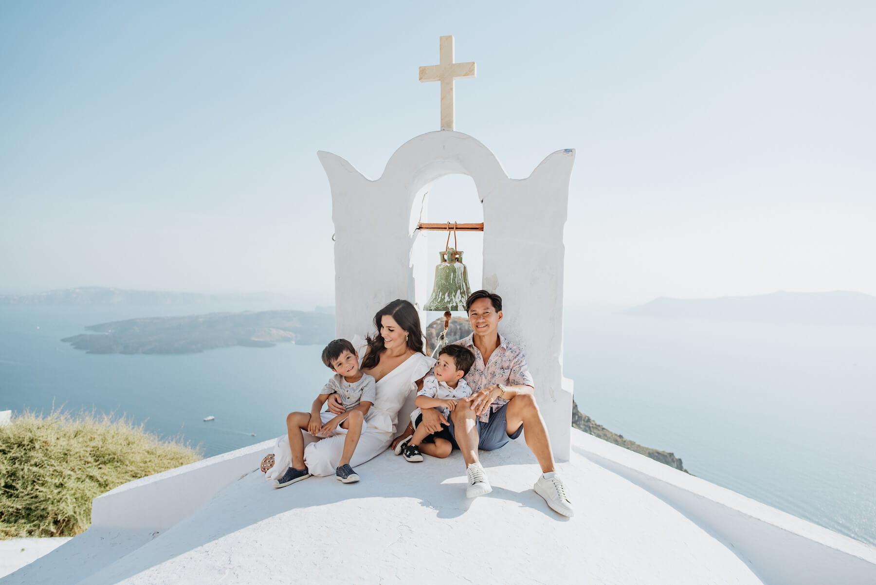 A mother, father and two young boys smile while sitting atop an iconic white church rooftop in Santorini, Greece.