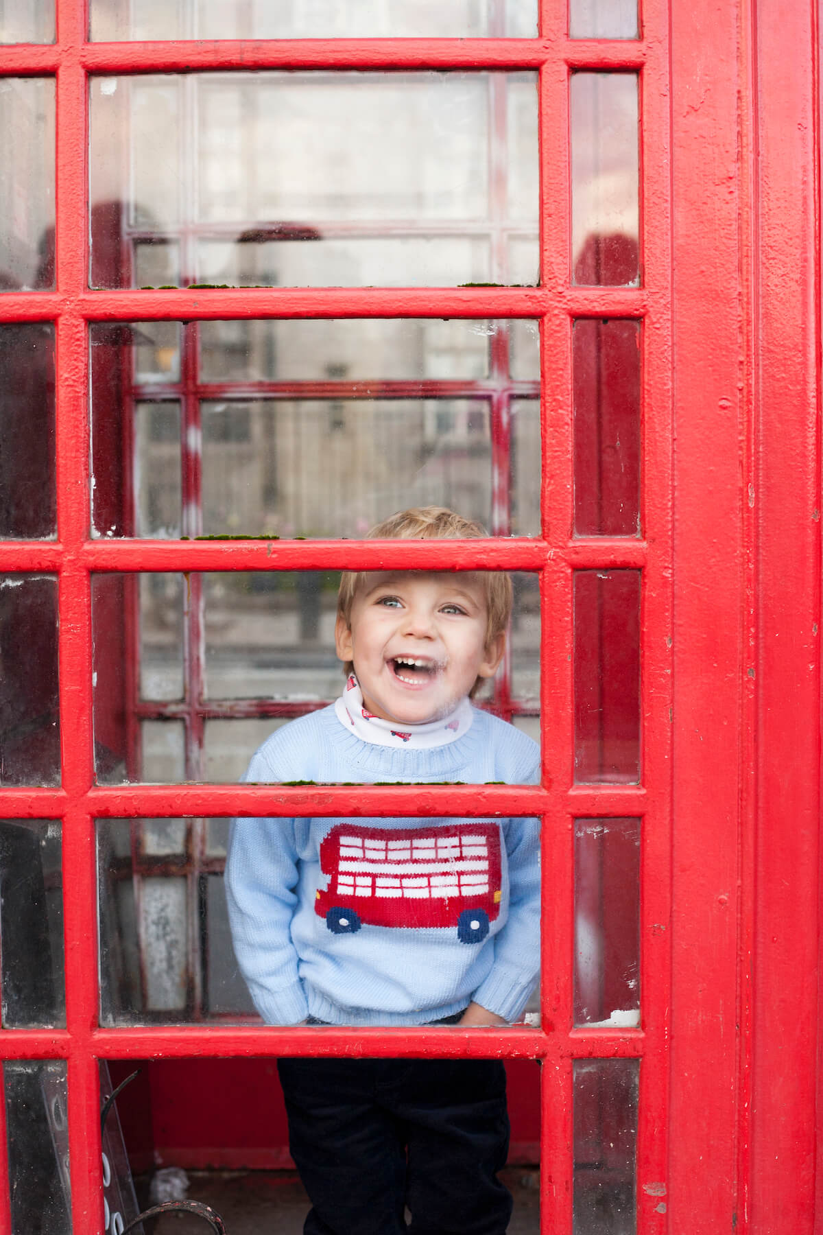 Boy laughing inside of a telephone booth in London England