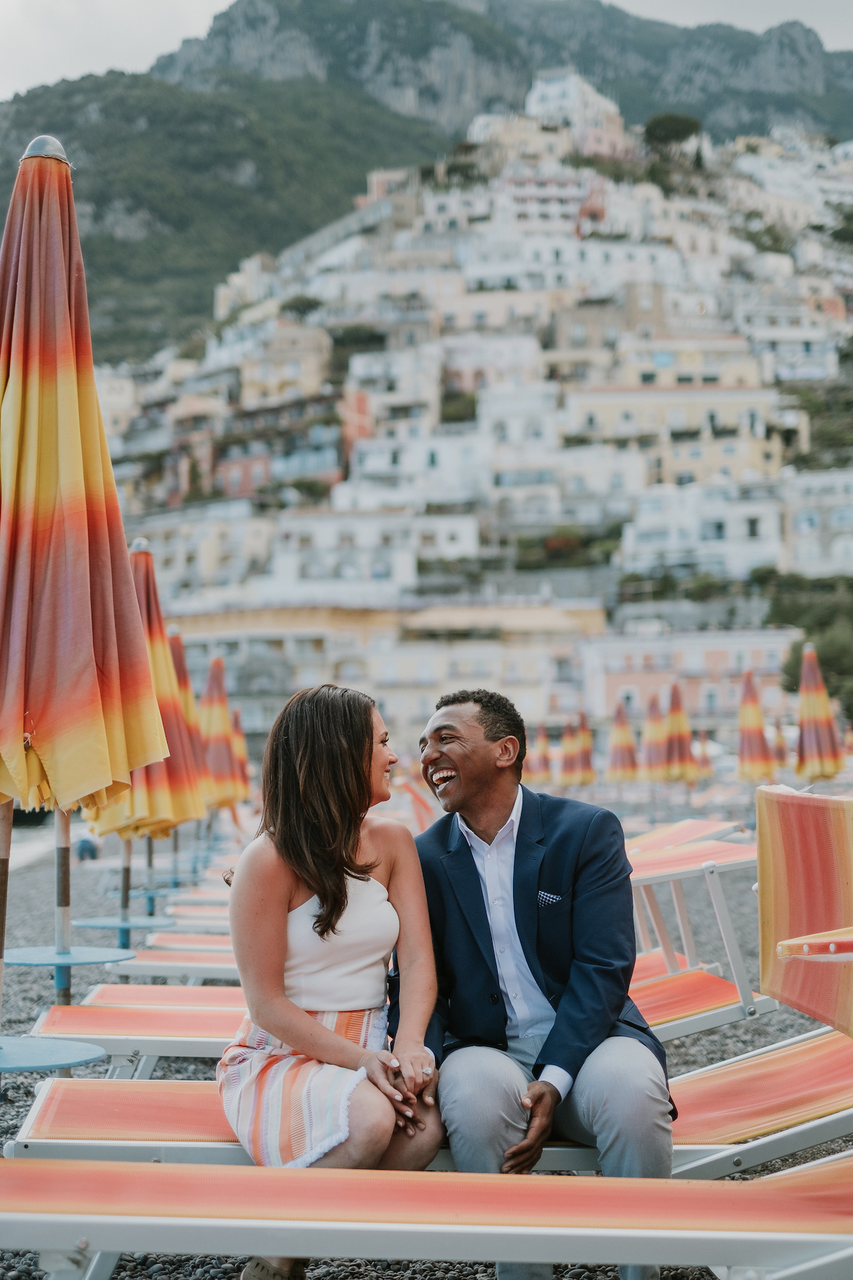A man and woman holding hands and laughing with each other while sitting on colourful beach chairs in front of the mountain houses in Positano, Italy.