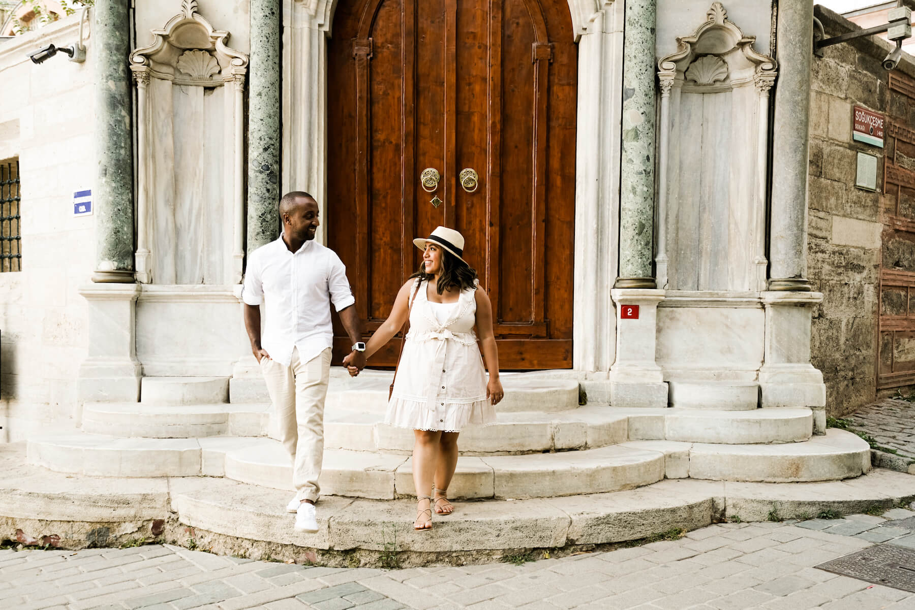 A man and a woman, both wearing white outfits, hold hands while descending some stone stairs in Istanbul, Turkey.