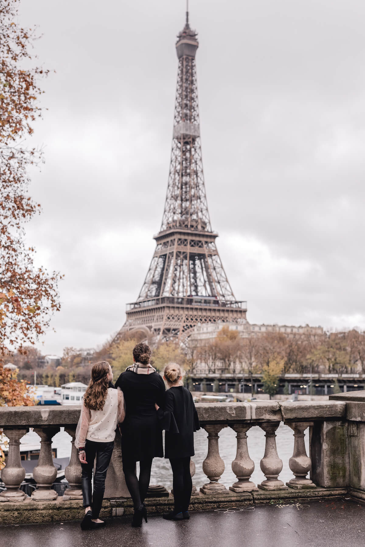Mom and daughters in Paris France in front of the Eiffel Tower