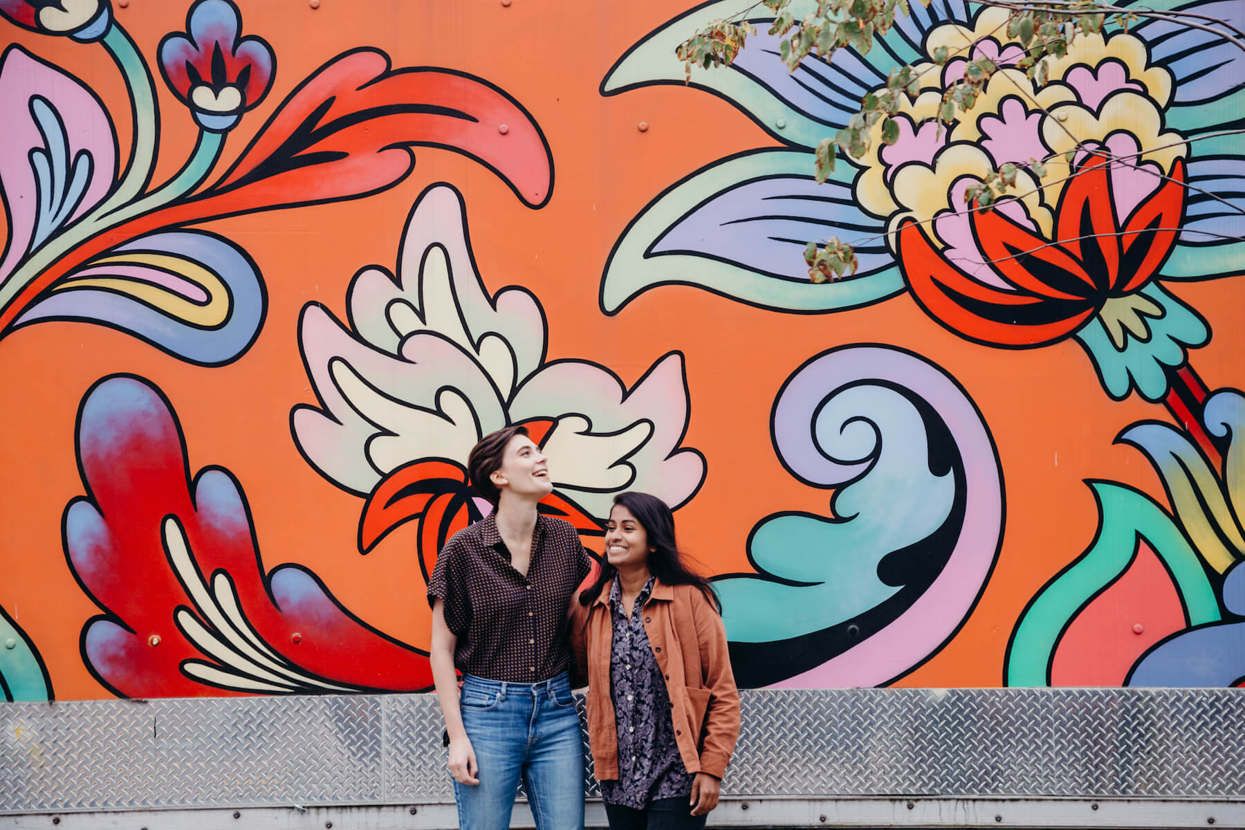 couple standing in front of a colorful wall in Portland, Oregon