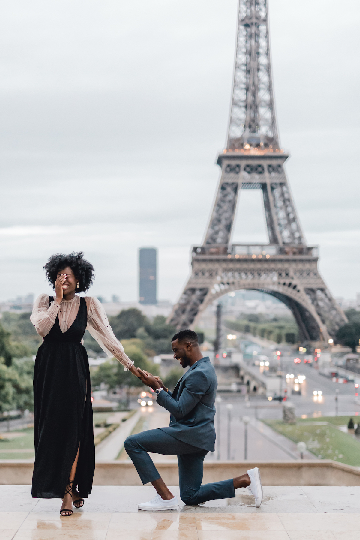 A woman smiles and holds her hand over her eyes while her boyfriend kneels in front of her with a ring, proposing to her in front of the Eiffel Tower in Paris, France.