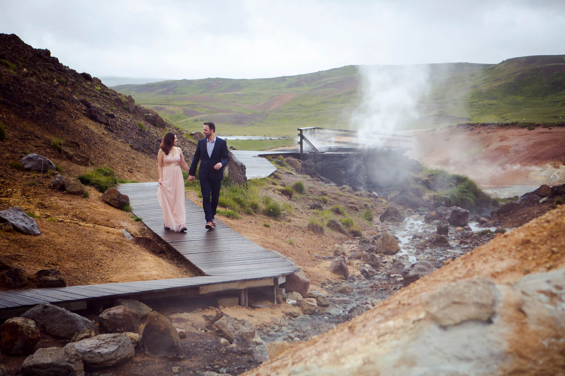 A well-dressed man and woman holding hands and walking by a steaming geyser in the rugged landscape close to Reykjavik, Iceland.