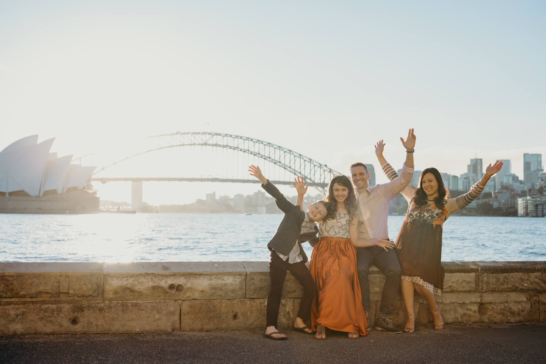 Family of 4 excited in front of the Sydney opera house in Australia
