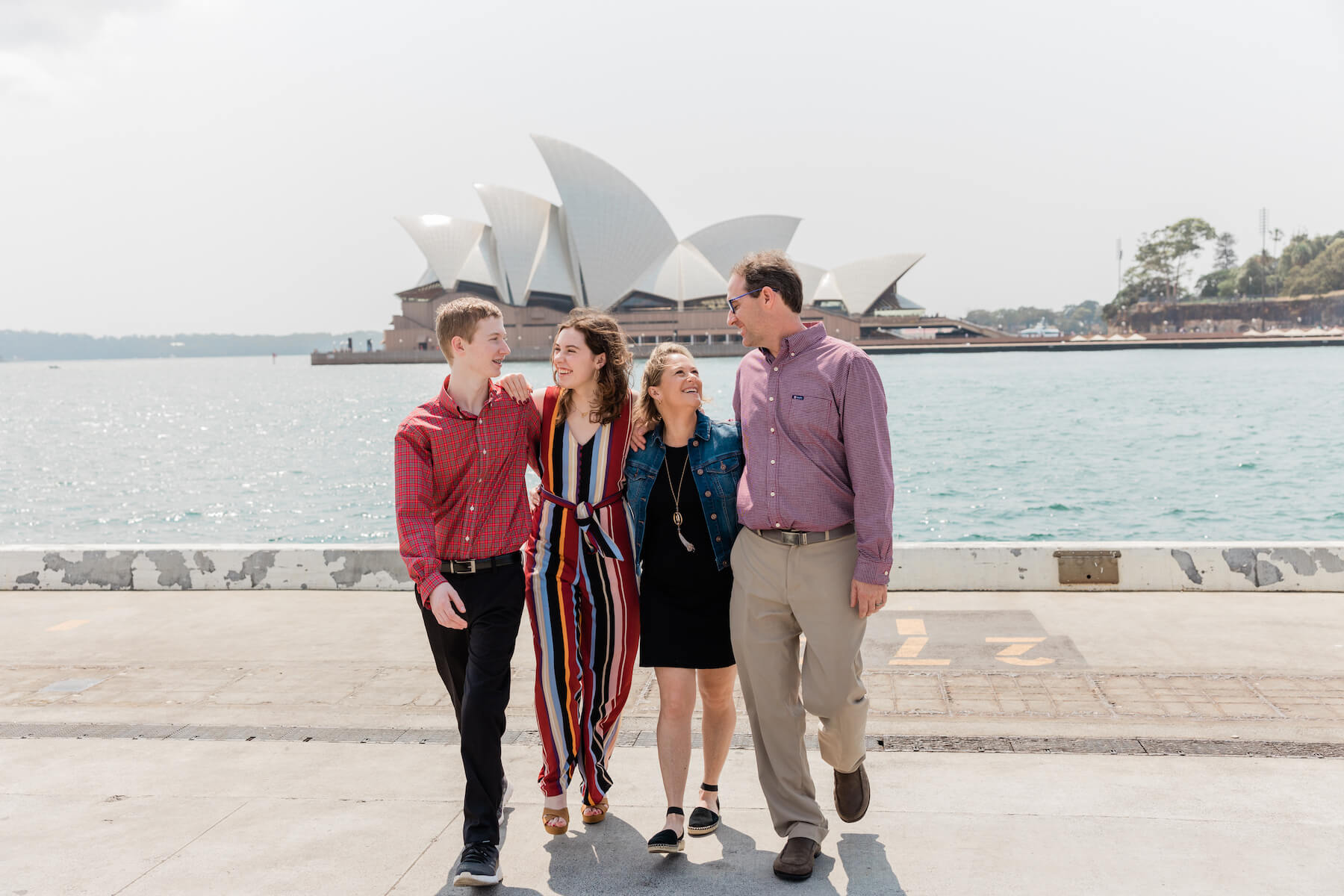 Family of 4 walking with the Sydney Opera house in Australia behind them
