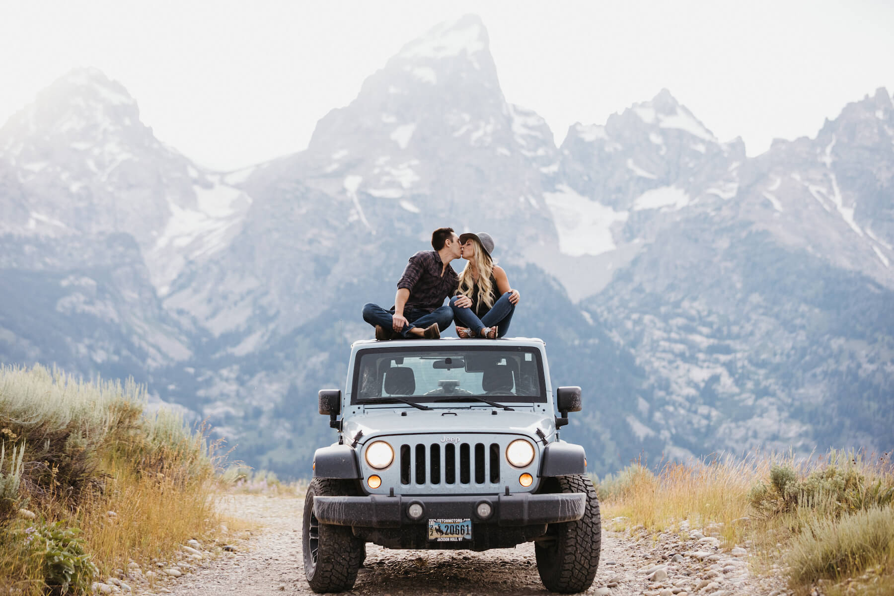Couple kissing on a jeep in Jackson Hole on a Flytographer photo shoot