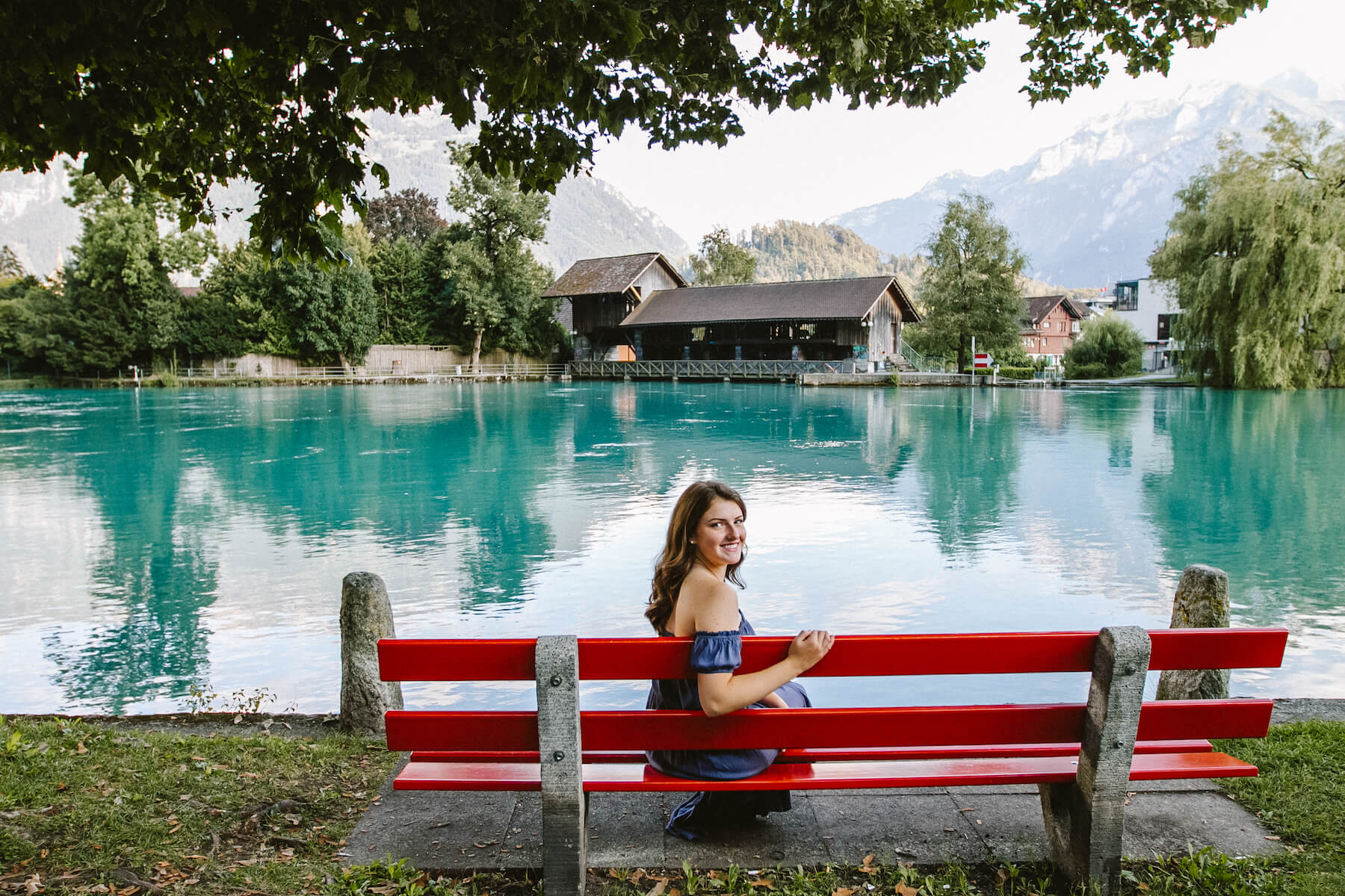 A young woman sitting on a bright red park bench, smiling while posing in front of a glacier-blue lake and mountains in Zurich, Switzerland.
