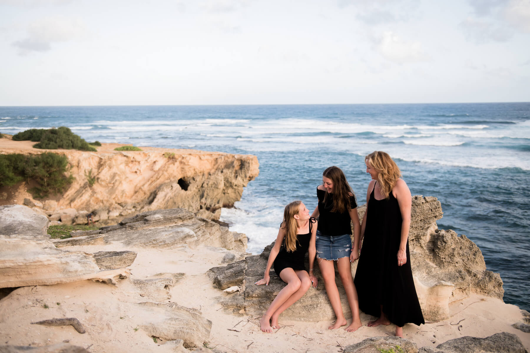 Mother and daughters on a cliff in Kauai Hawaii