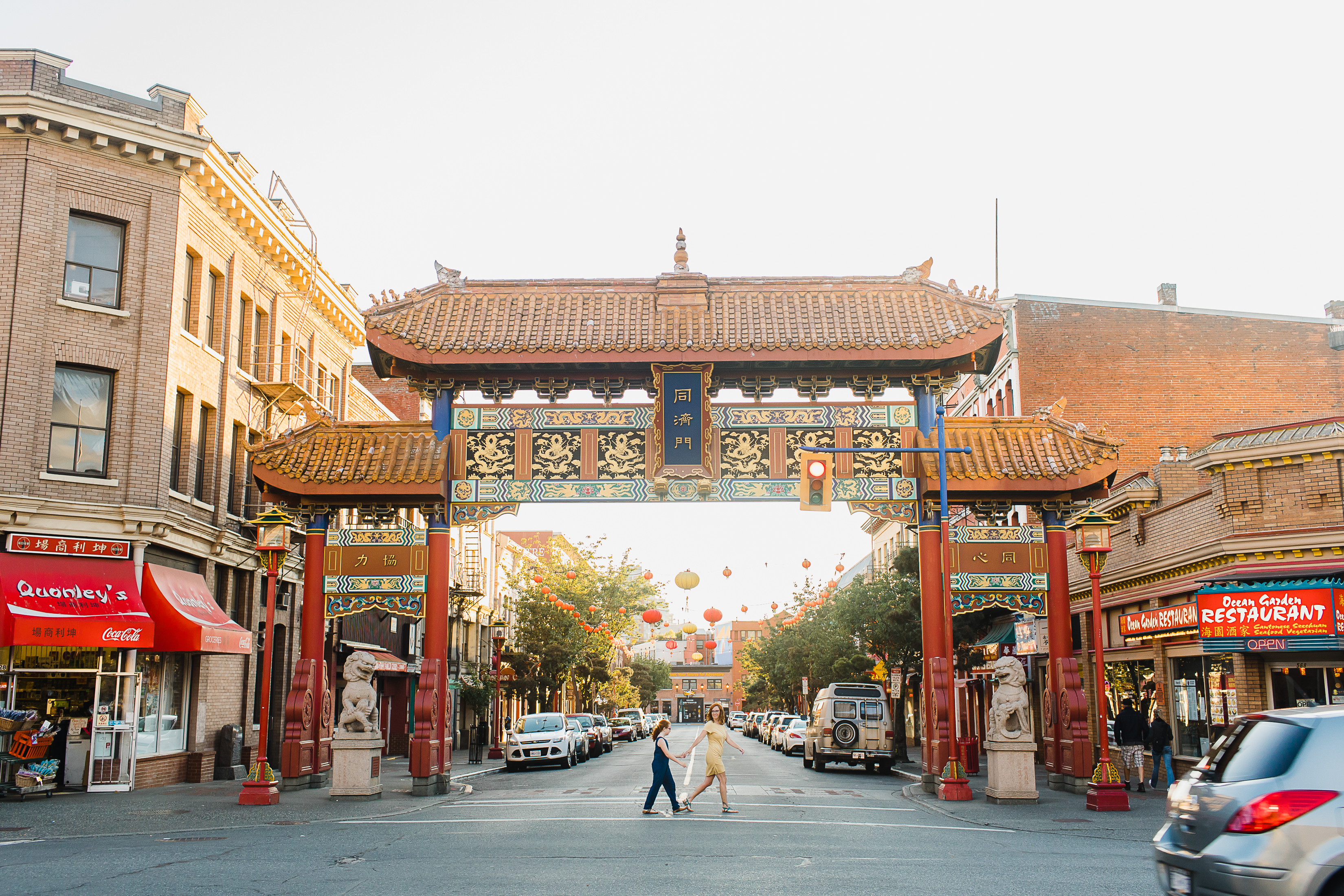 Two people running across the street in front of the Chinatown gates in Victoria BC