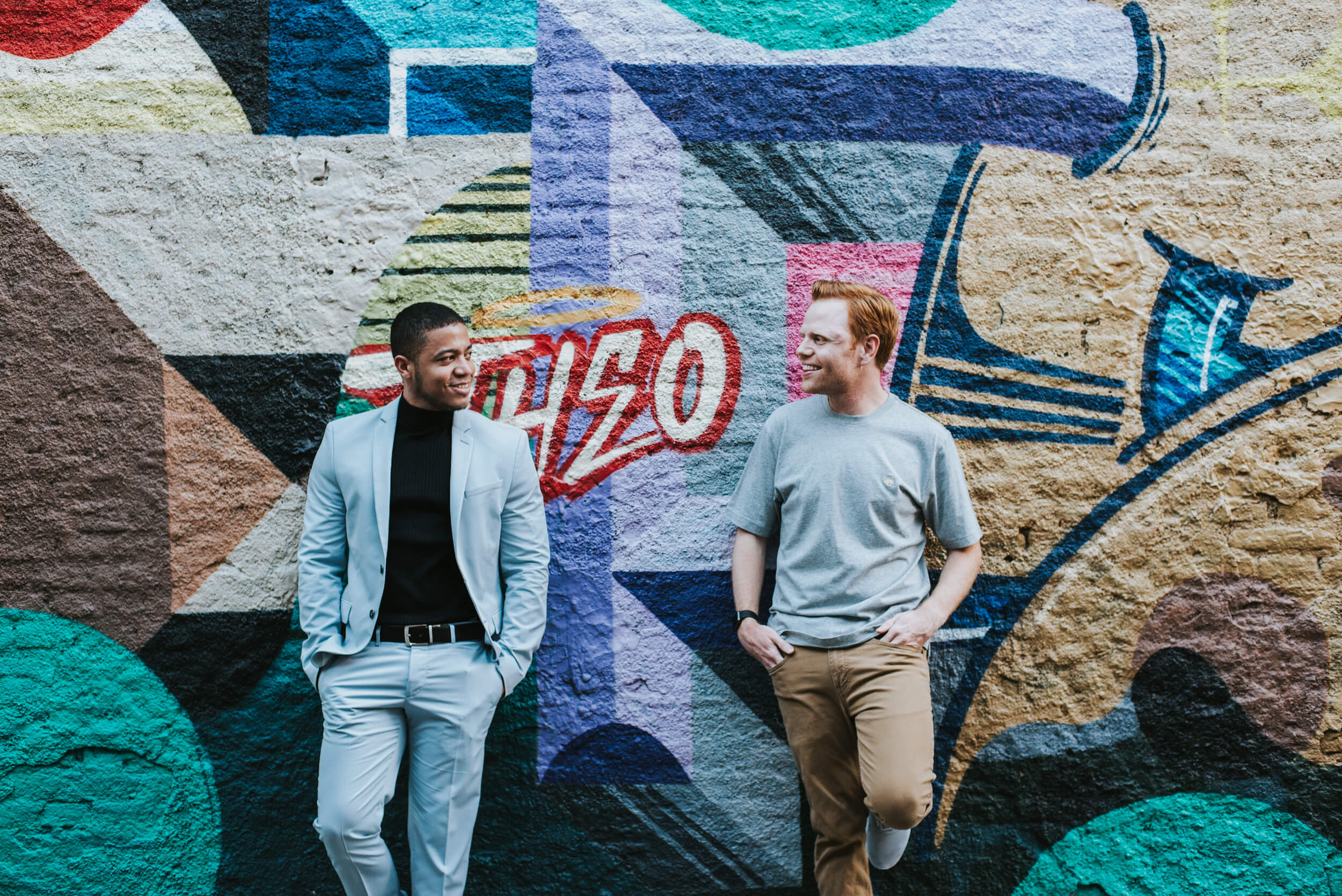 Two men stand in front of a colourful painted wall in Buenos Aires, Argentina.