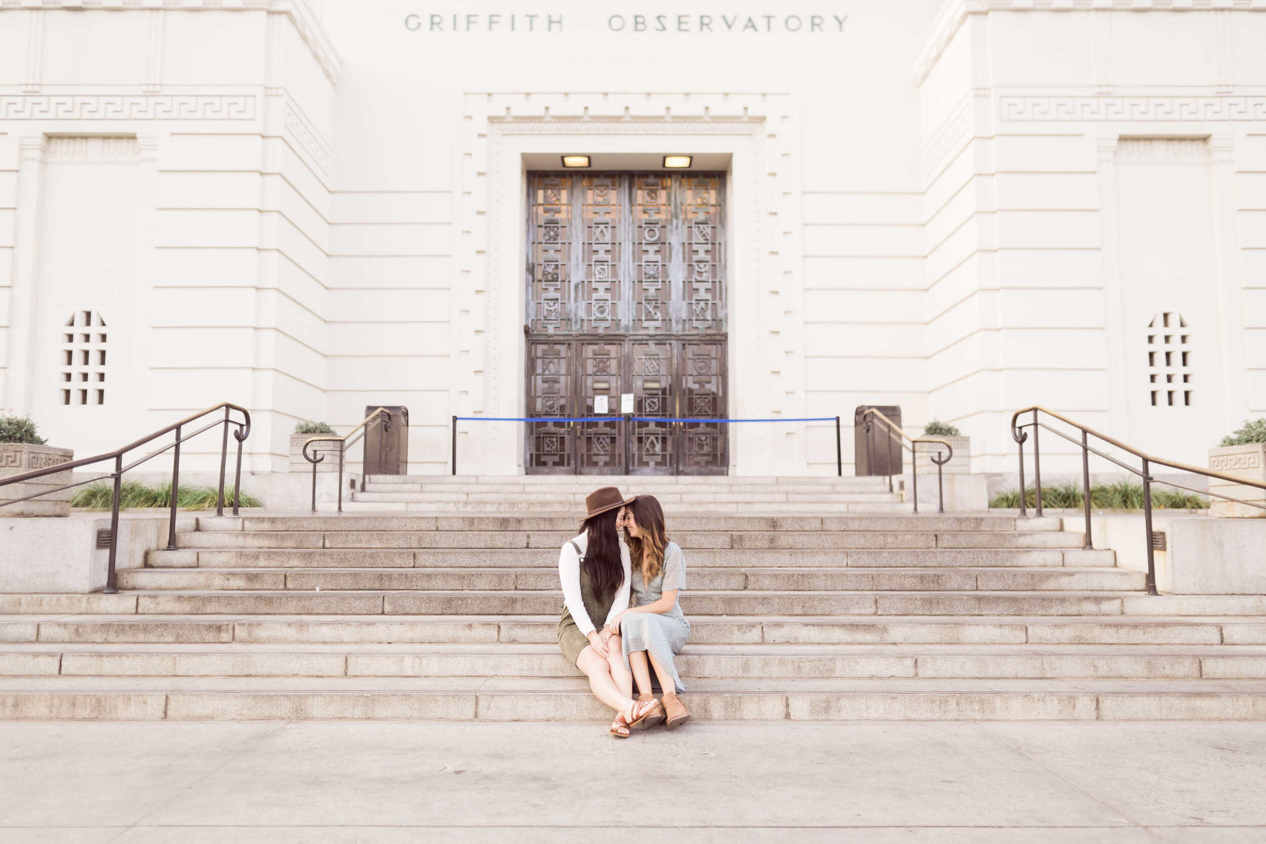 A female couple snuggles on the steps of the Griffith Observatory in Los Angeles, USA.
