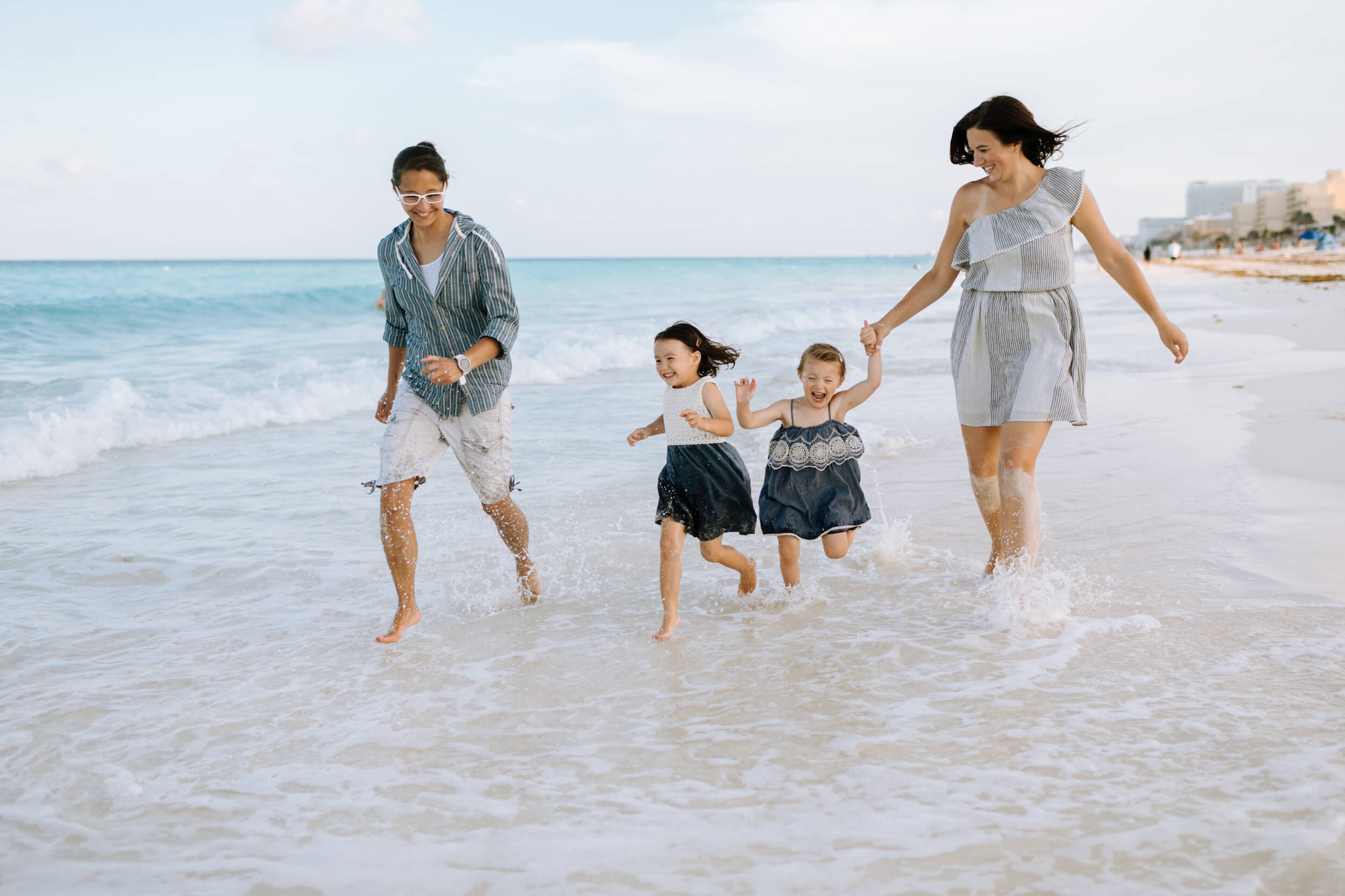 Two moms and their little girls run in the surf in Cancun, Mexico.
