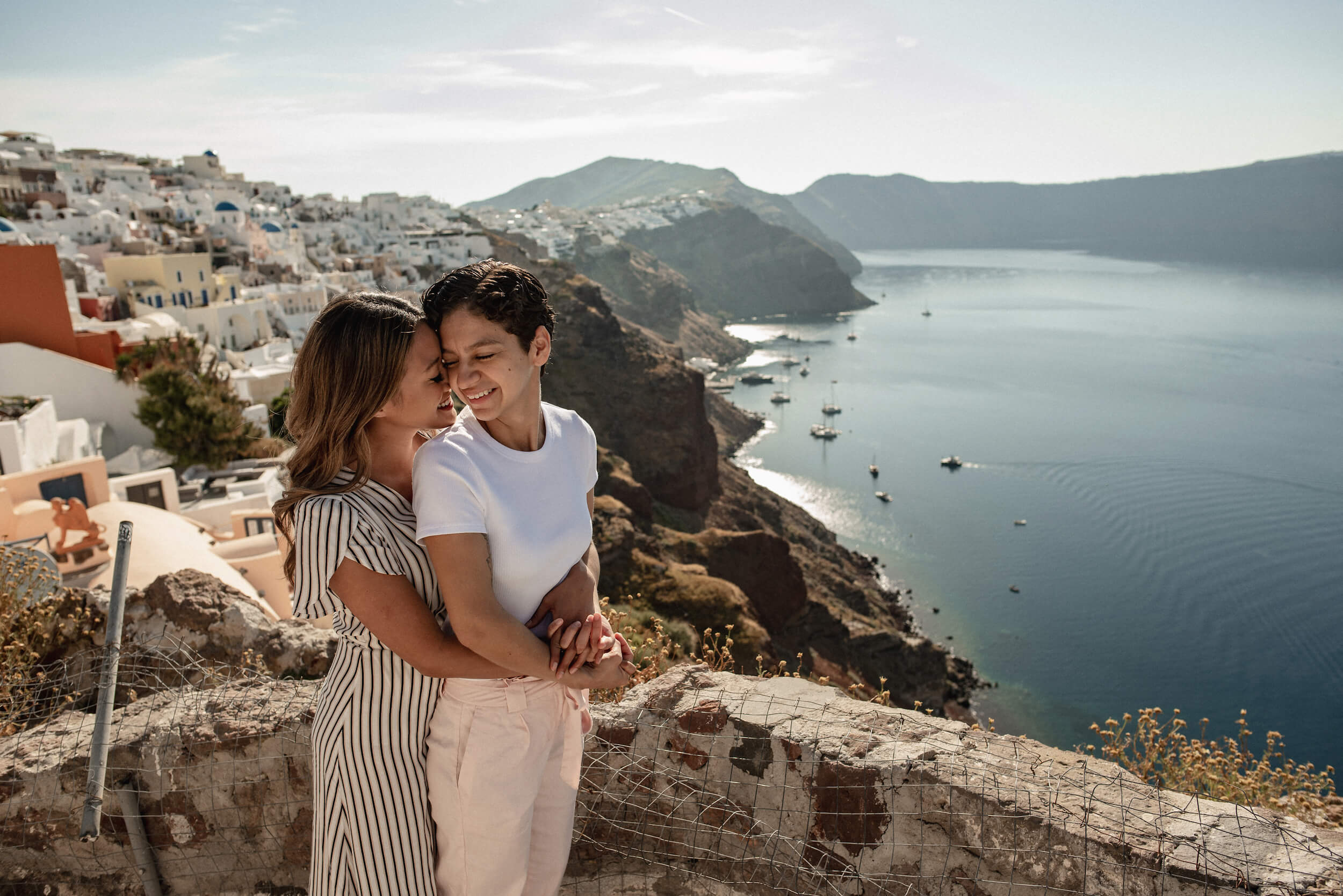 Two lovers embrace in front of the iconic blue domes in Santorini, Greece.