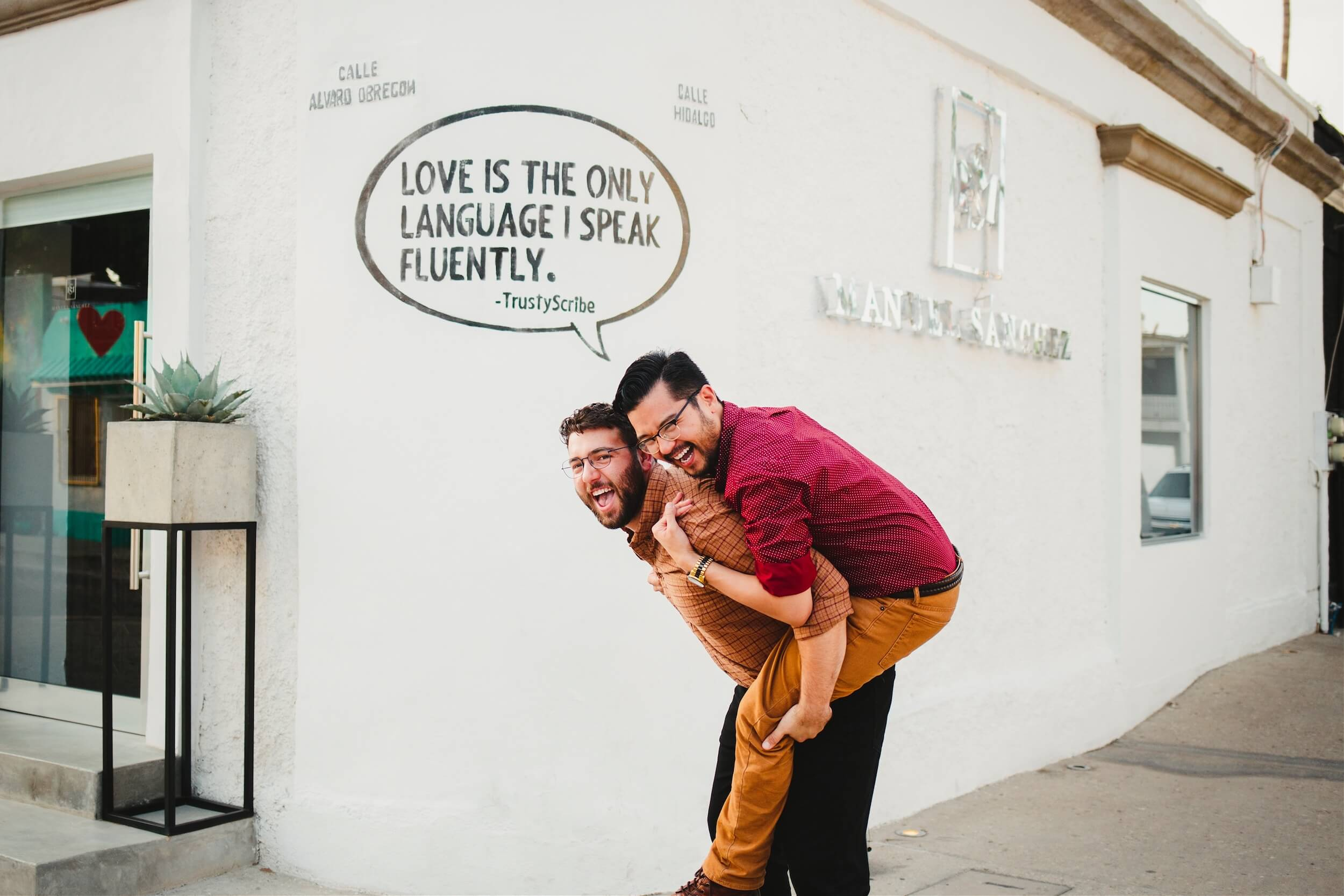 A male couple laughs in front of a painted wall in Cabo San Lucas, Mexico.